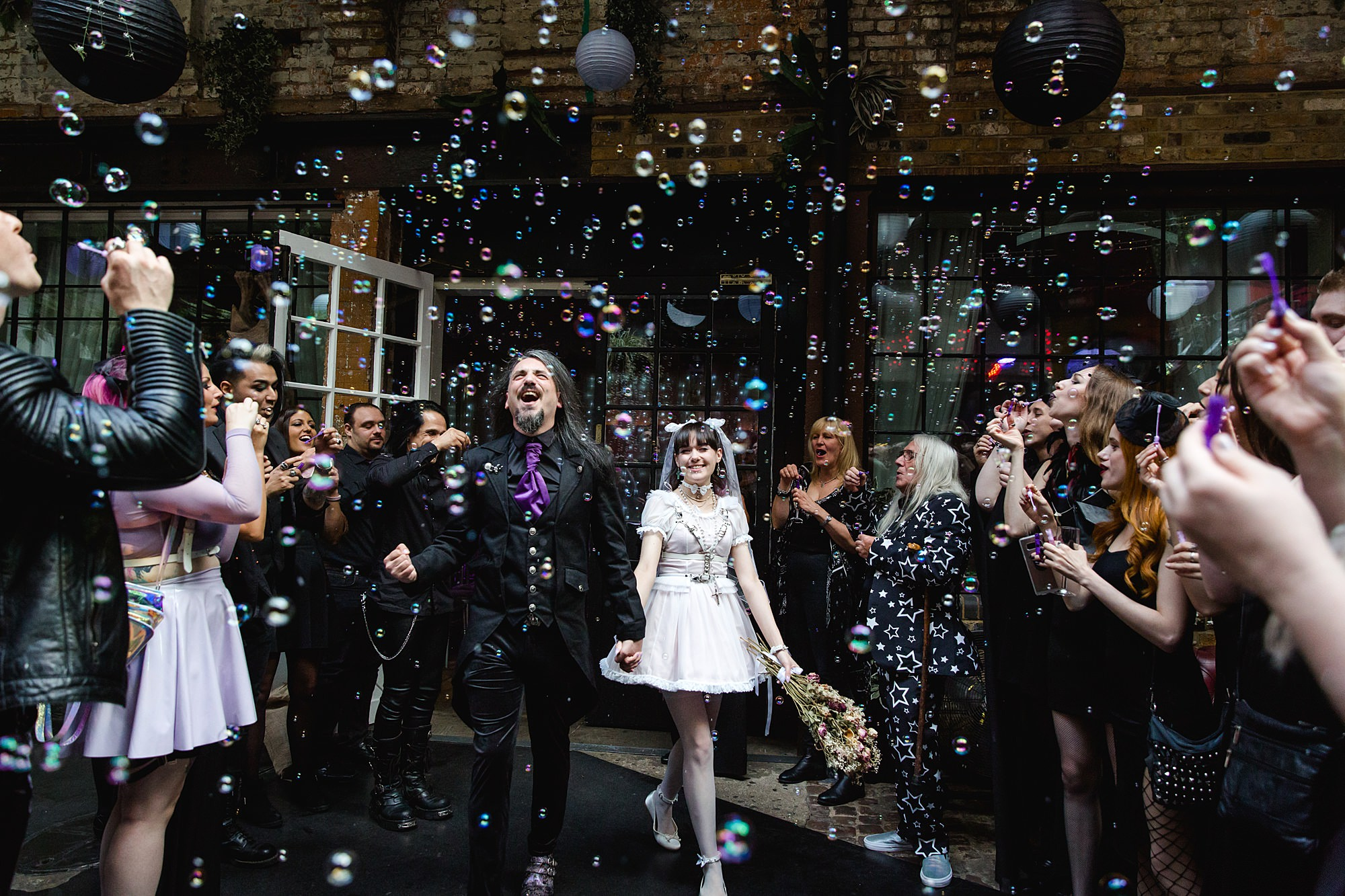 bride and groom walk through bubble confetti at Gothic wedding London