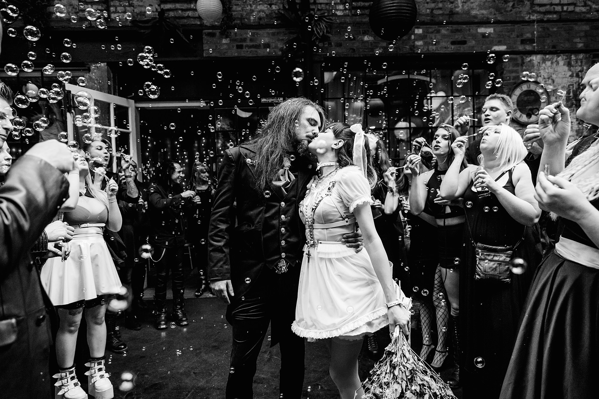 goth bride and groom kissing amongst bubbles