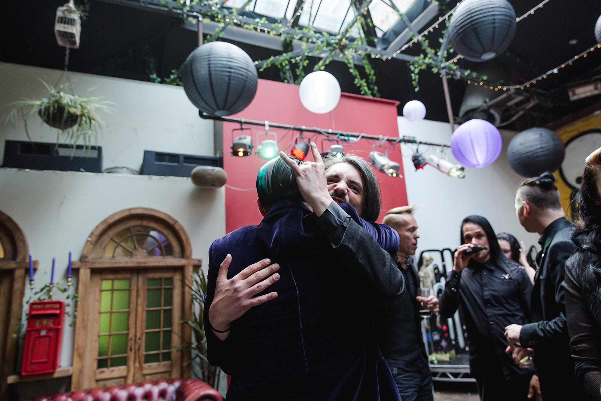 wedding guest hugging groom at goth wedding london