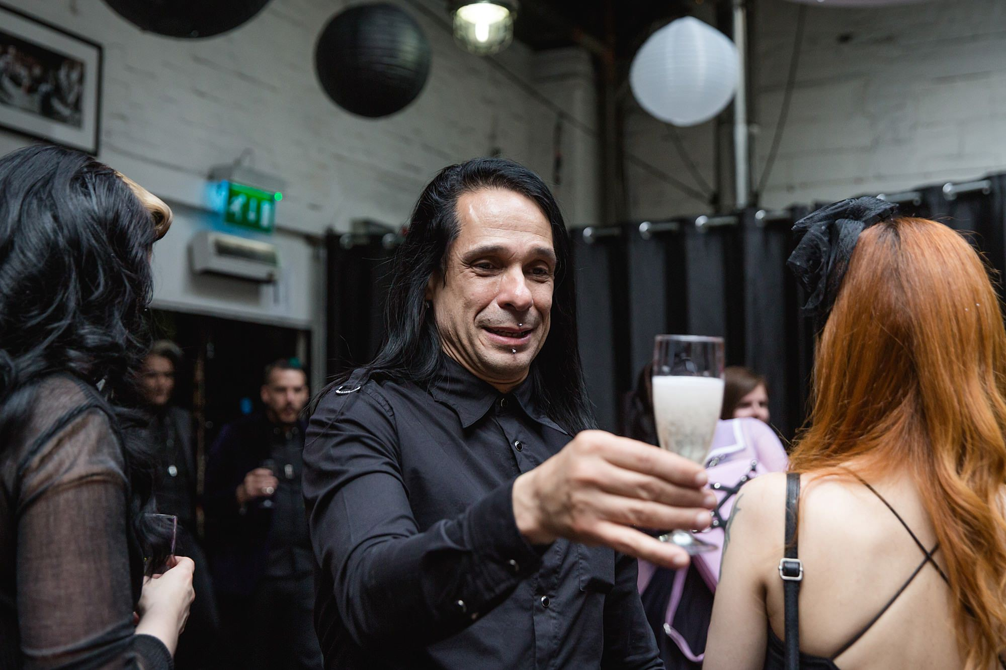 Gothic wedding London guest with prosecco drink