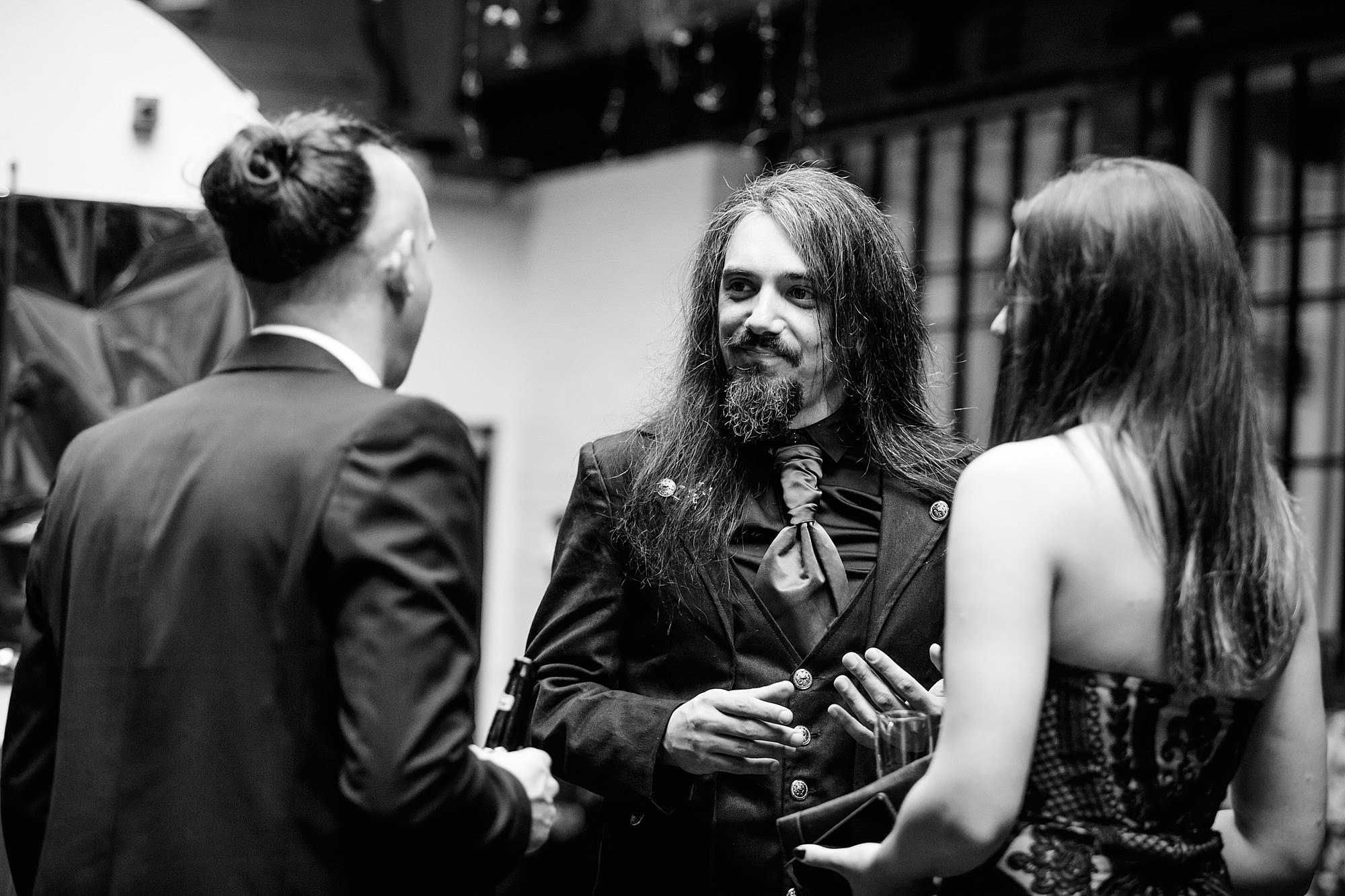groom chats to guests during goth wedding islington metalworks
