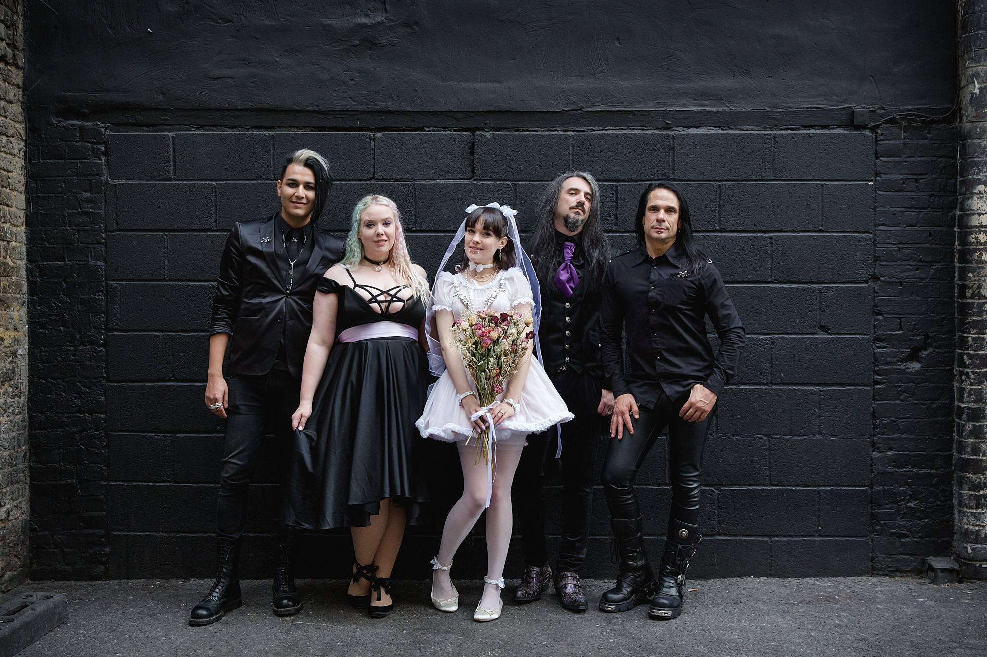 bride, groom and wedding party beside black wall at islington metalworks