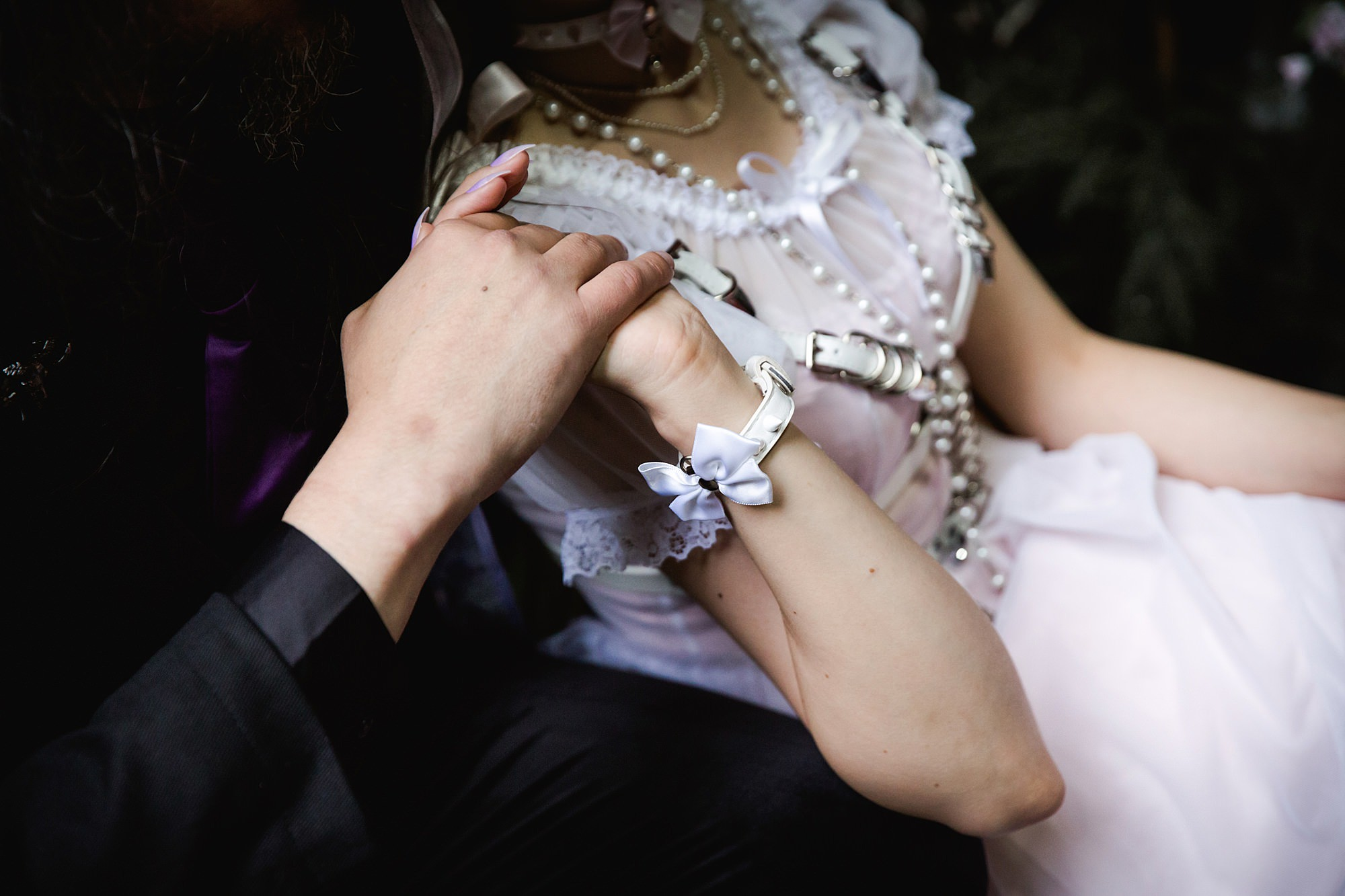 close up of bride's hand with wrist cuffs holding groom's hand a goth wedding