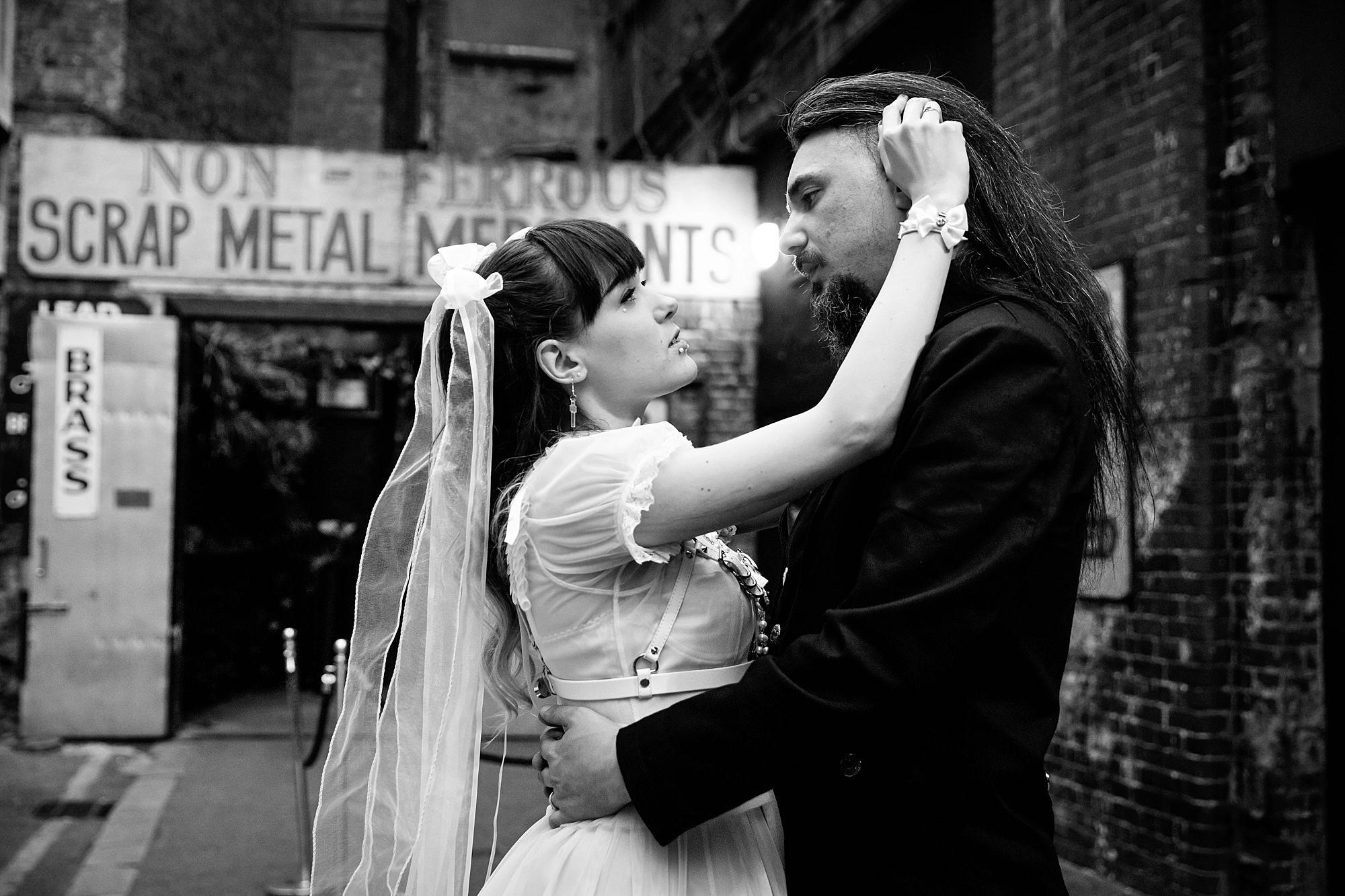 bride strokes groom's hair at gothic wedding london