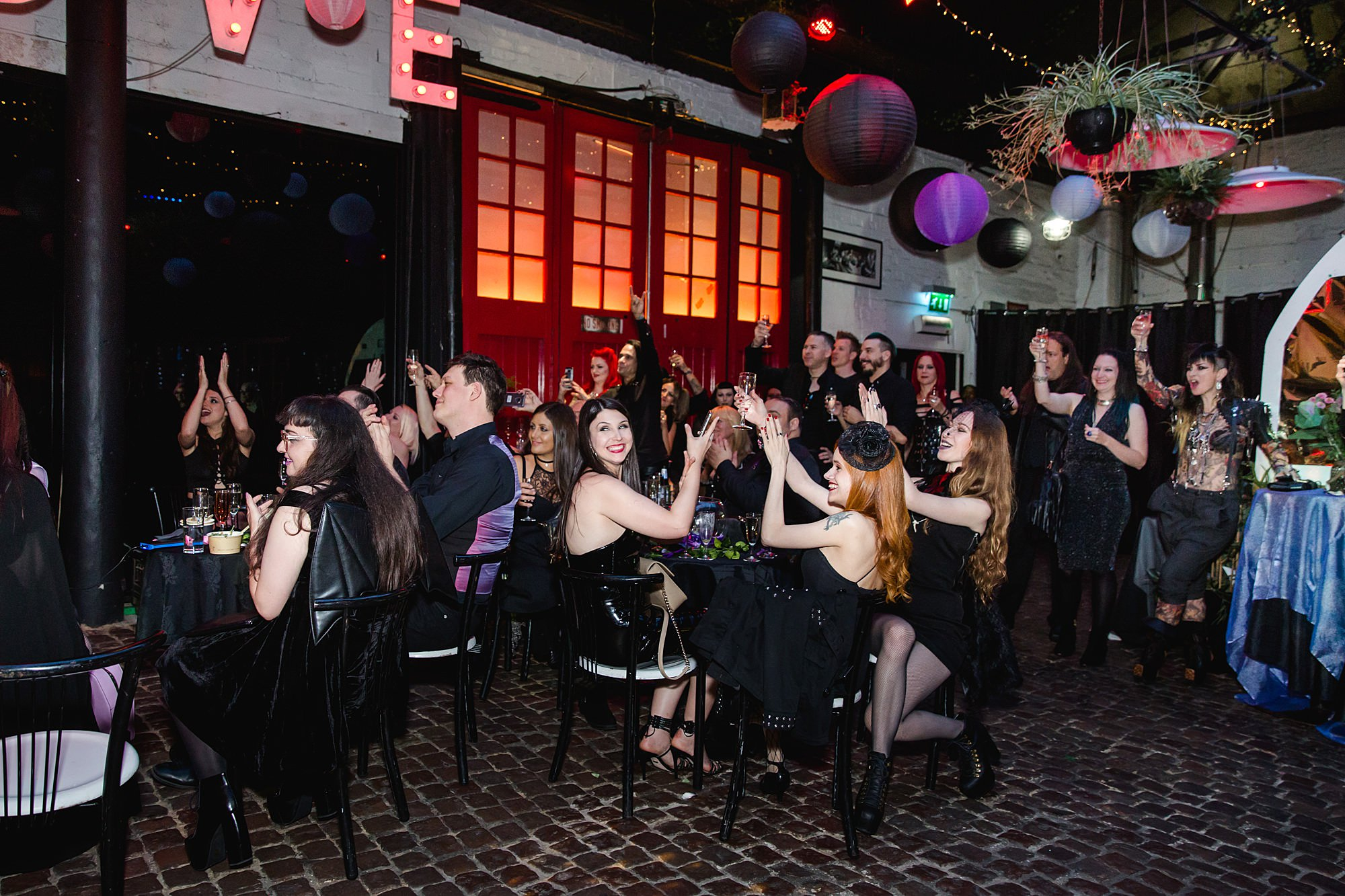 wedding guests cheering for speeches at Gothic wedding London