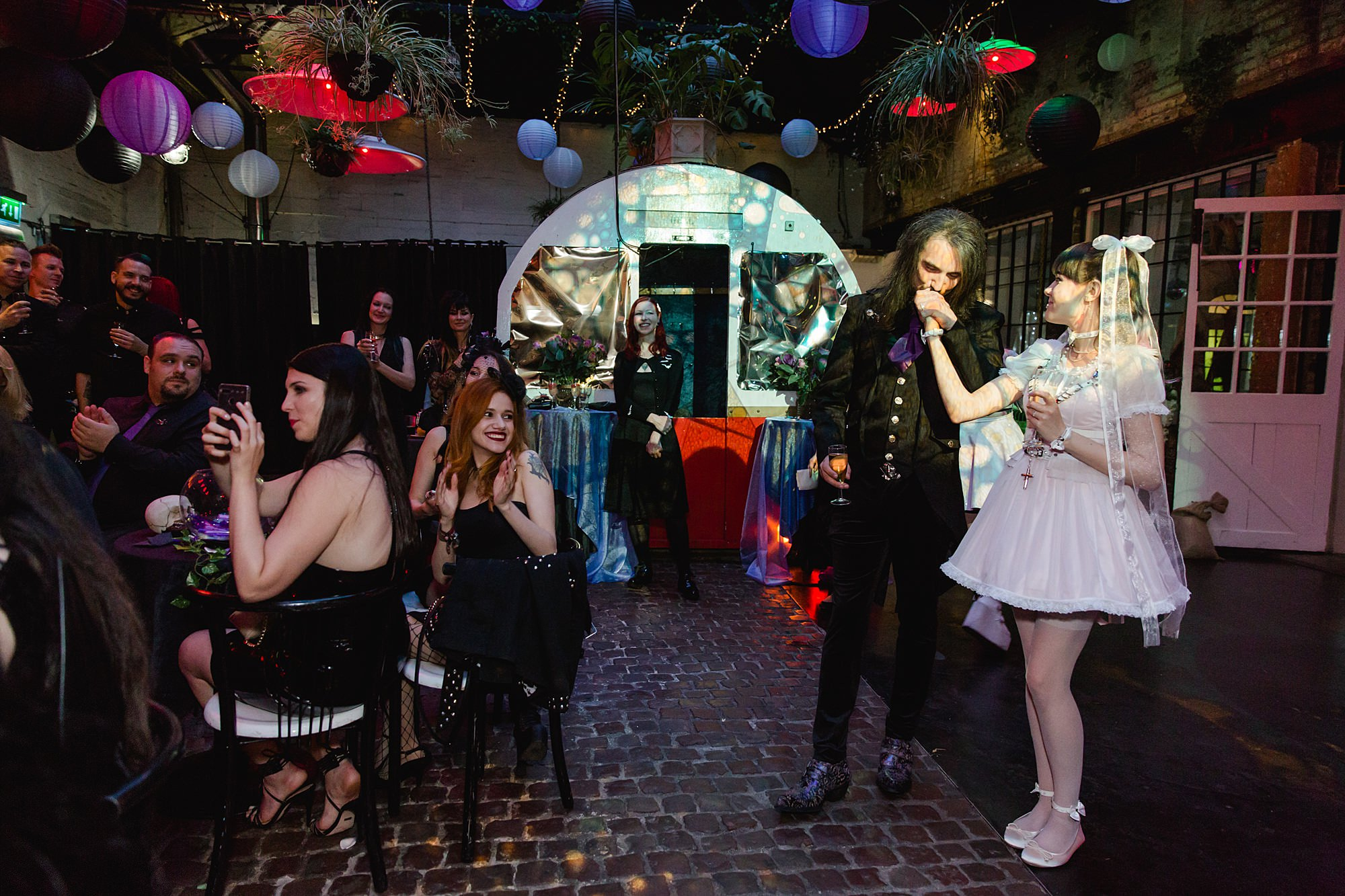 groom kisses bride during speeches at Gothic wedding London