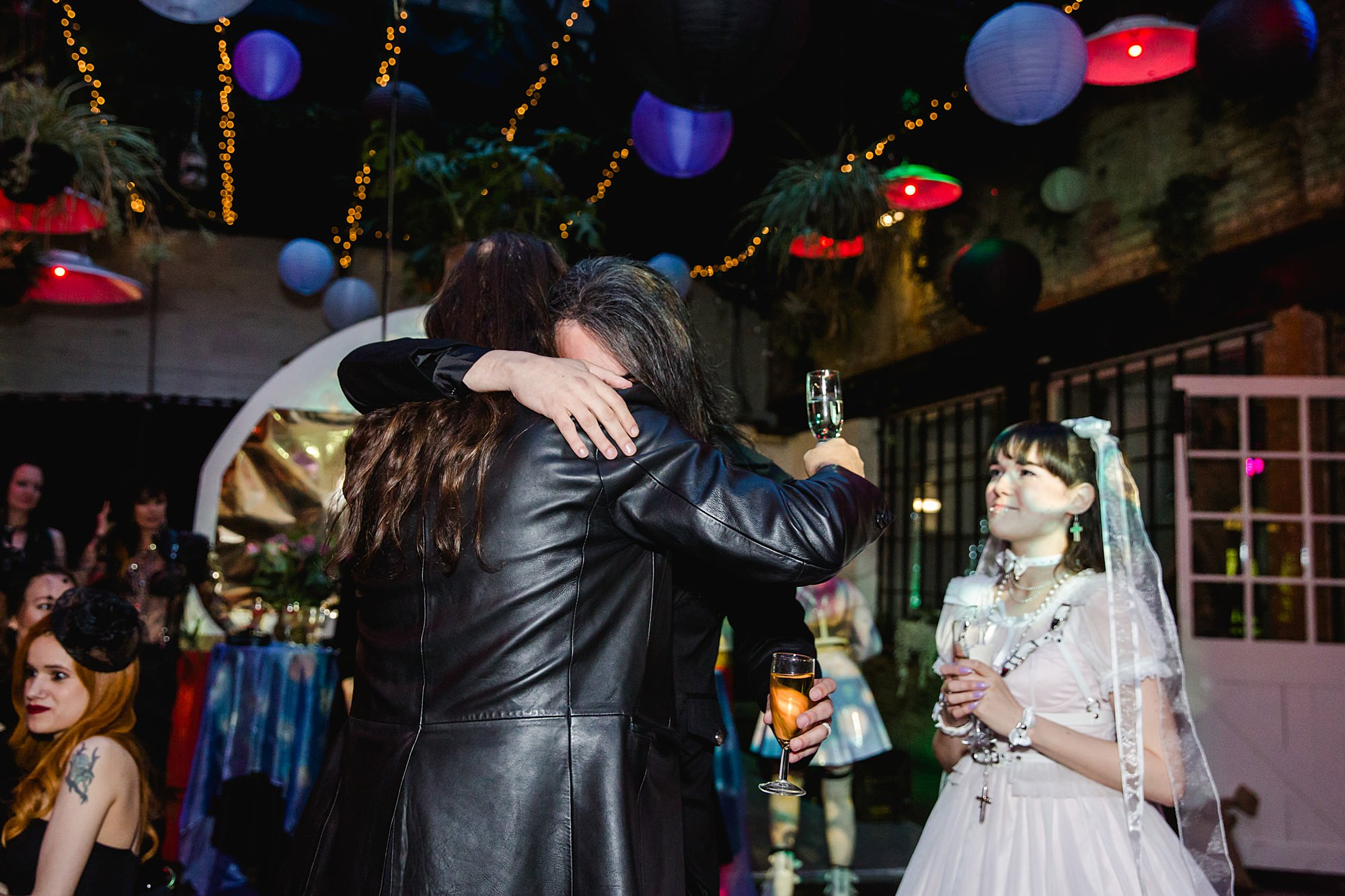 groom hugs guest after speech at islington metalworks gothic wedding