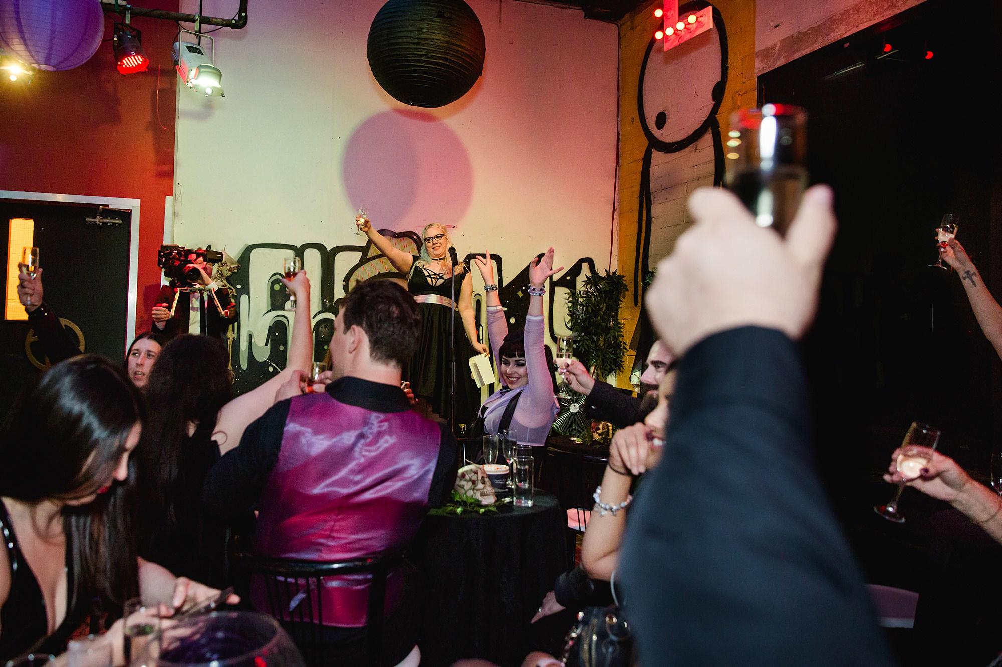 bridesmaid raises a toast during speeches at goth wedding london