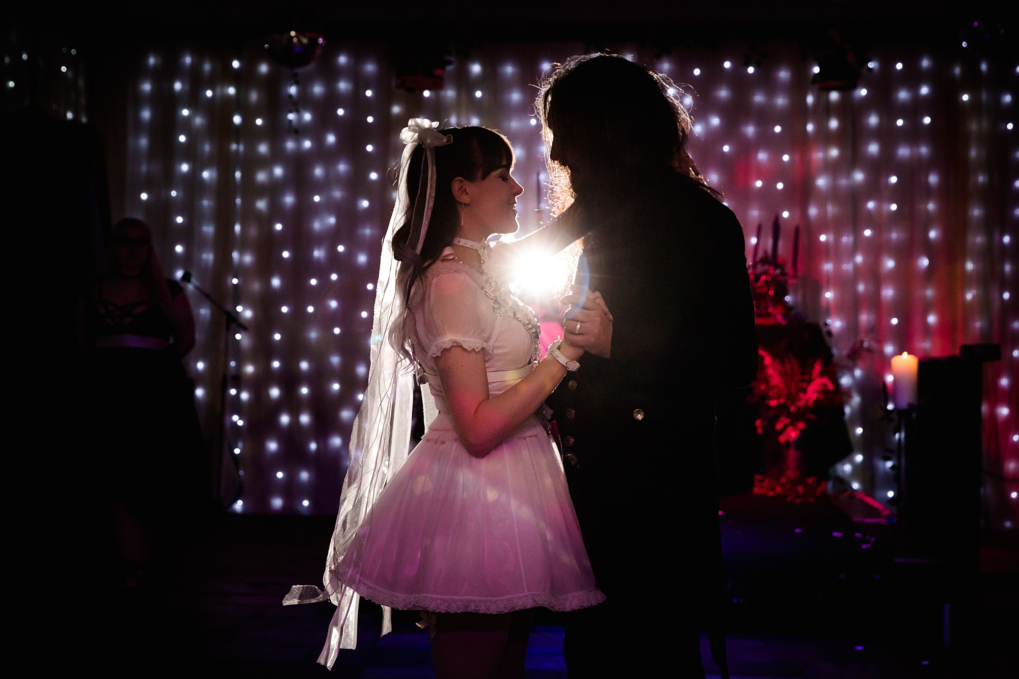 bride and groom's first dance in front of fairy lights at goth wedding