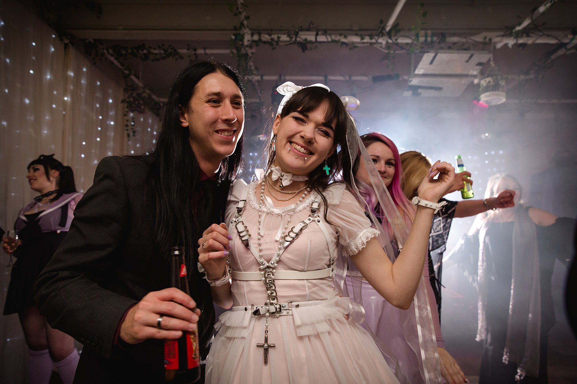 bride and guests dance together at goth wedding