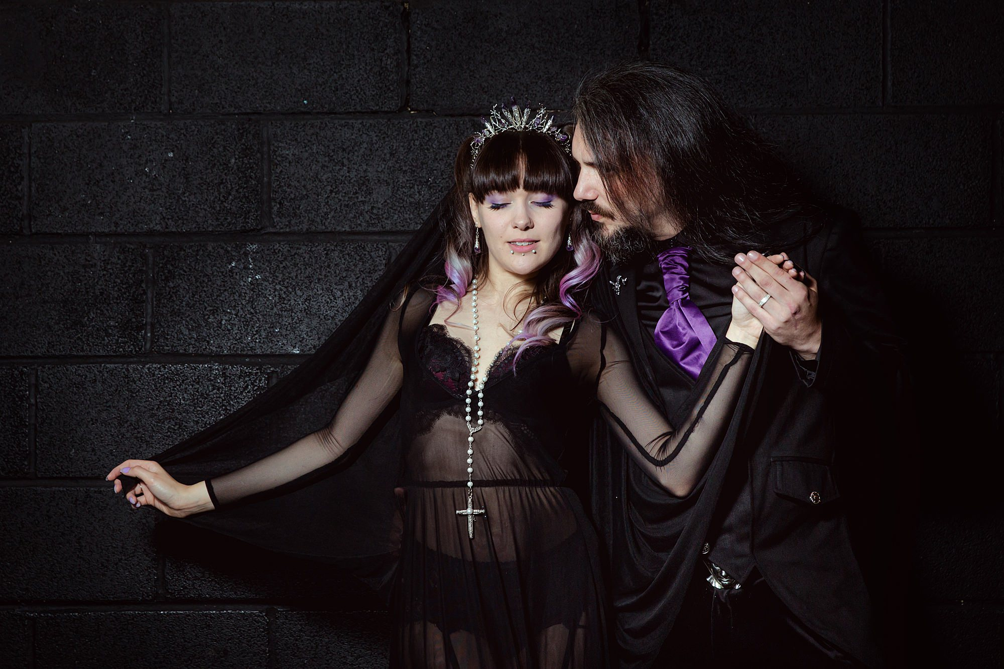 bride and groom pose together in black outfits in front of black wall at goth wedding