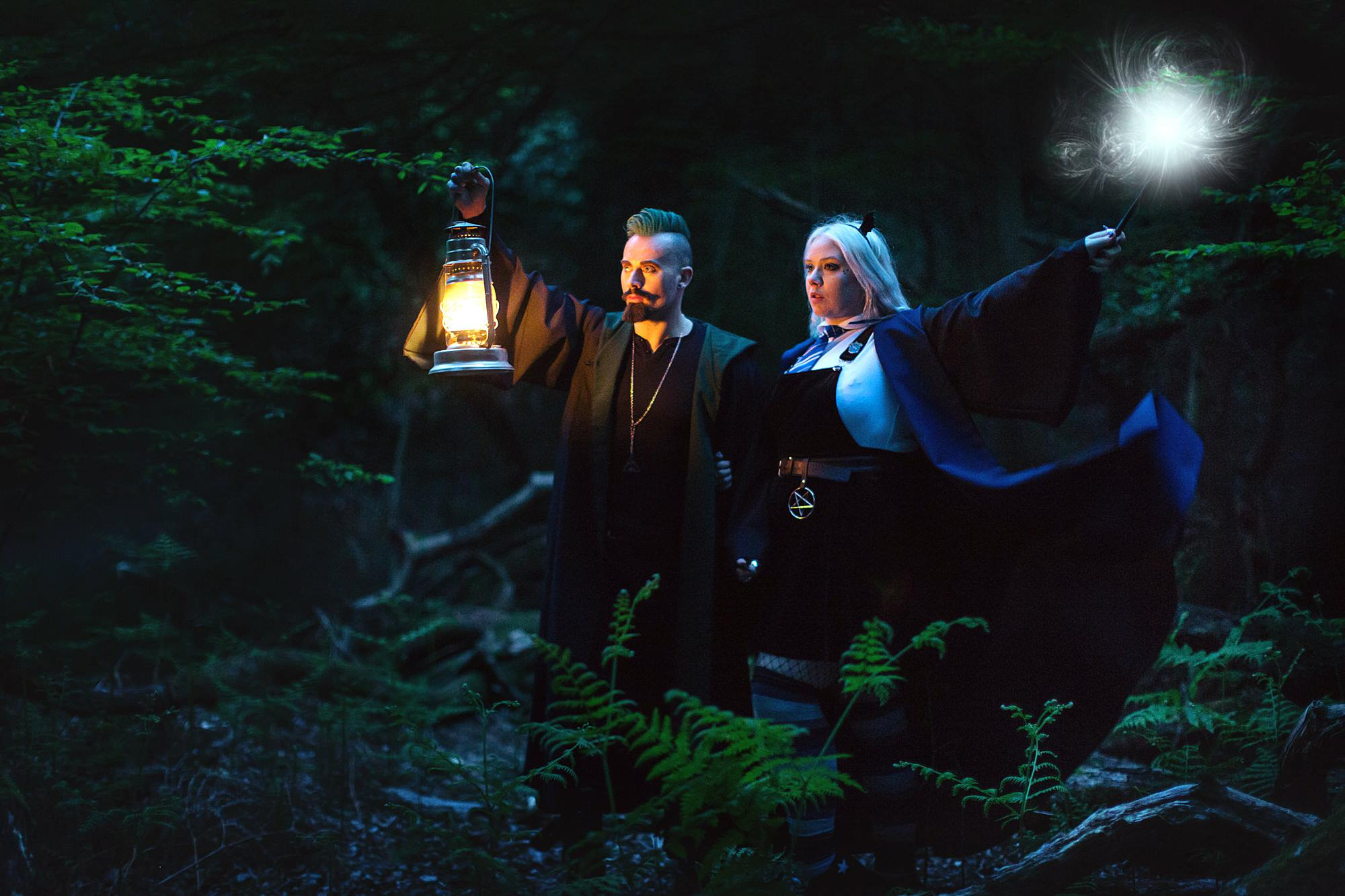 Harry Potter engagement shoot couple with lamps and wands in forest