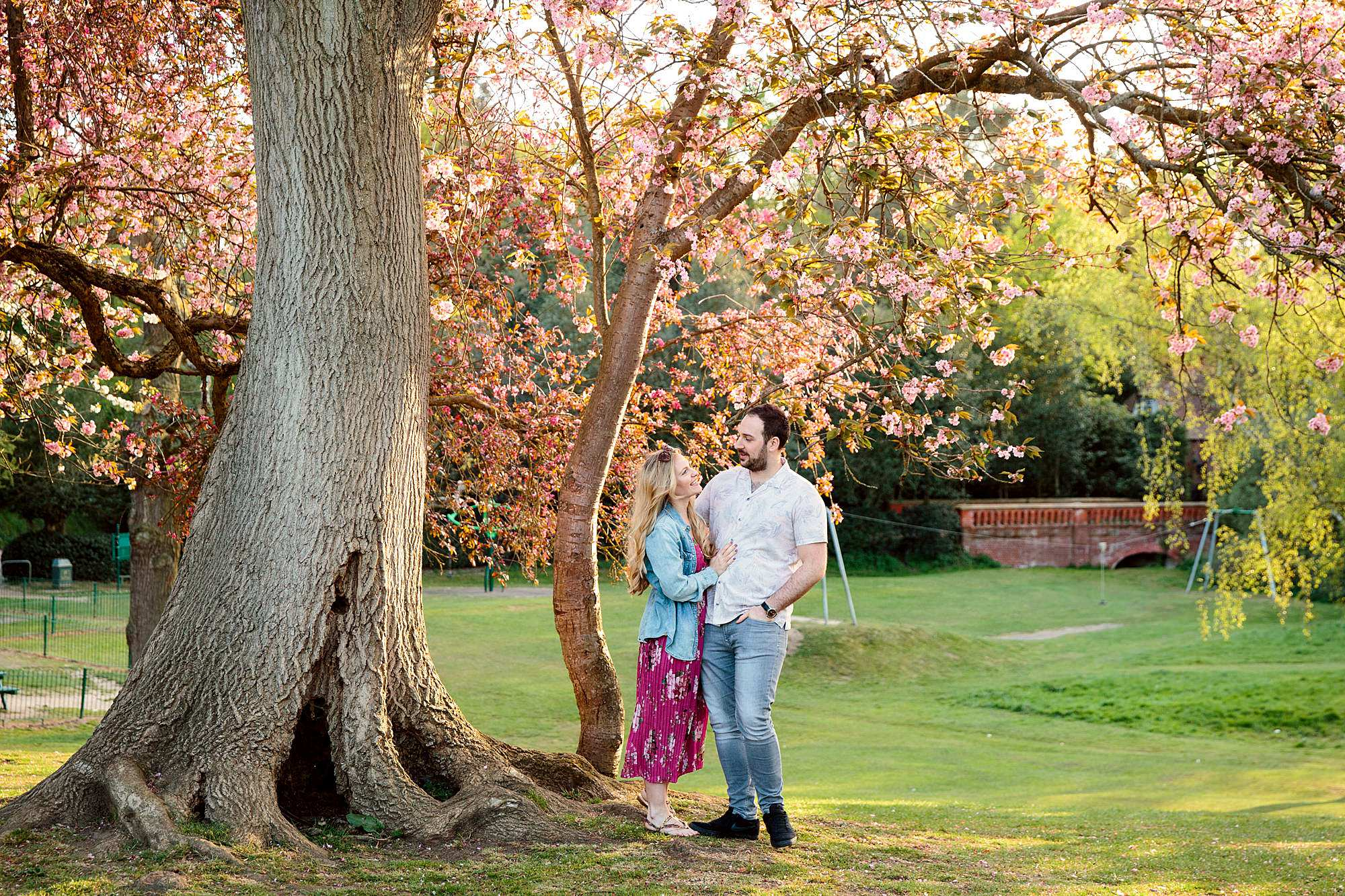 a couple stand together under a blossom tree
