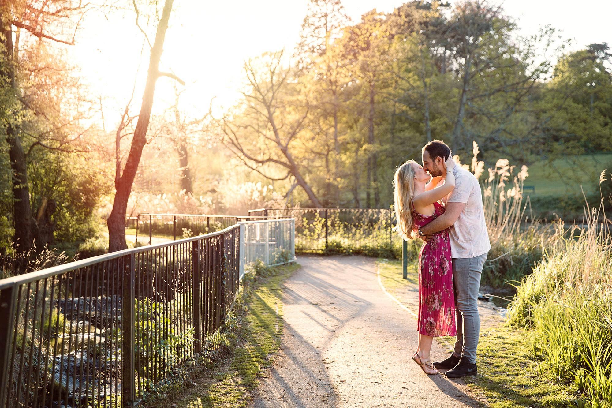 Summer evening engagement shoot couple kiss in sunlight