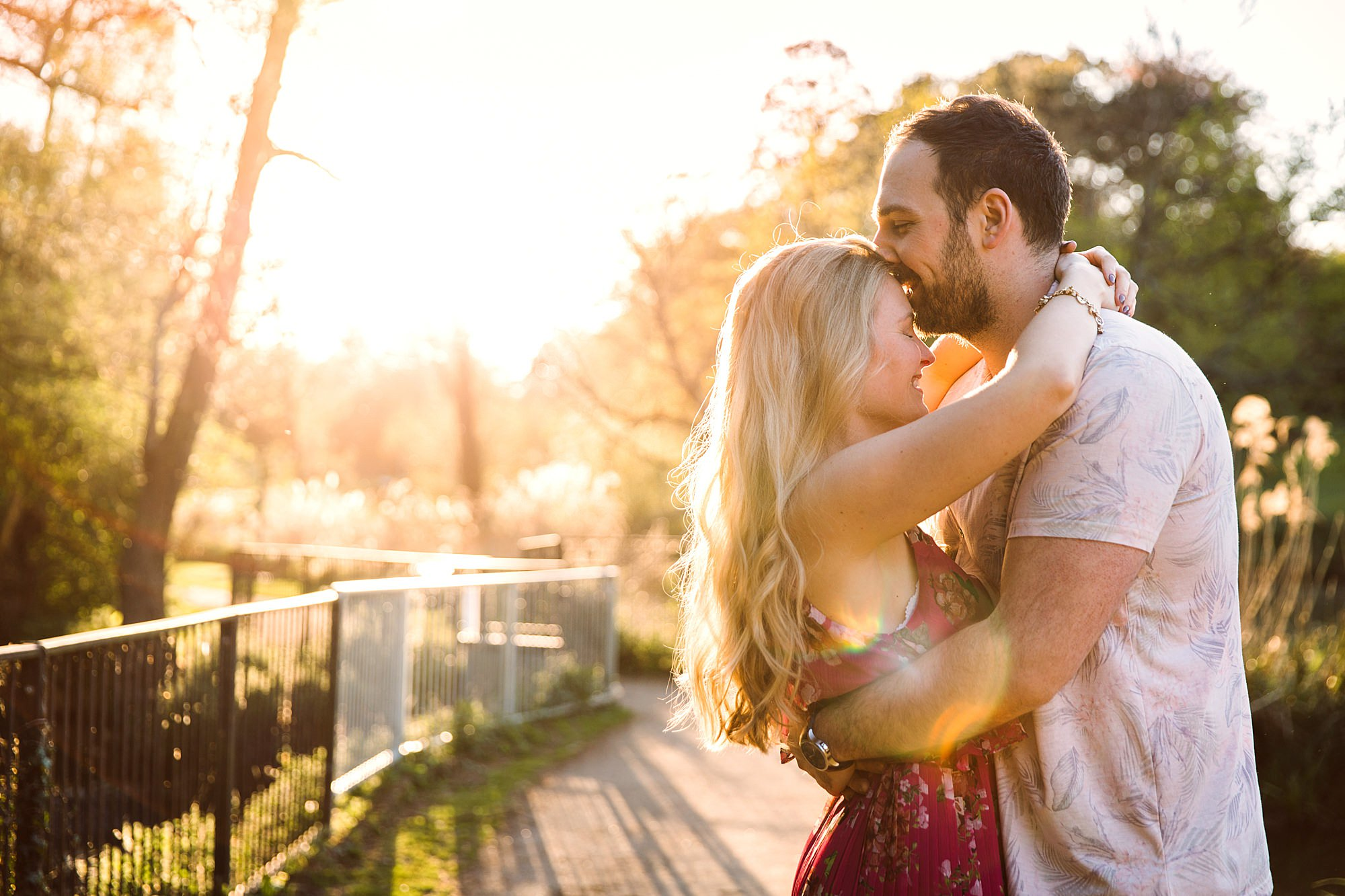 Summer evening engagement shoot groom kisses bride to be on forehead in bright sunlight
