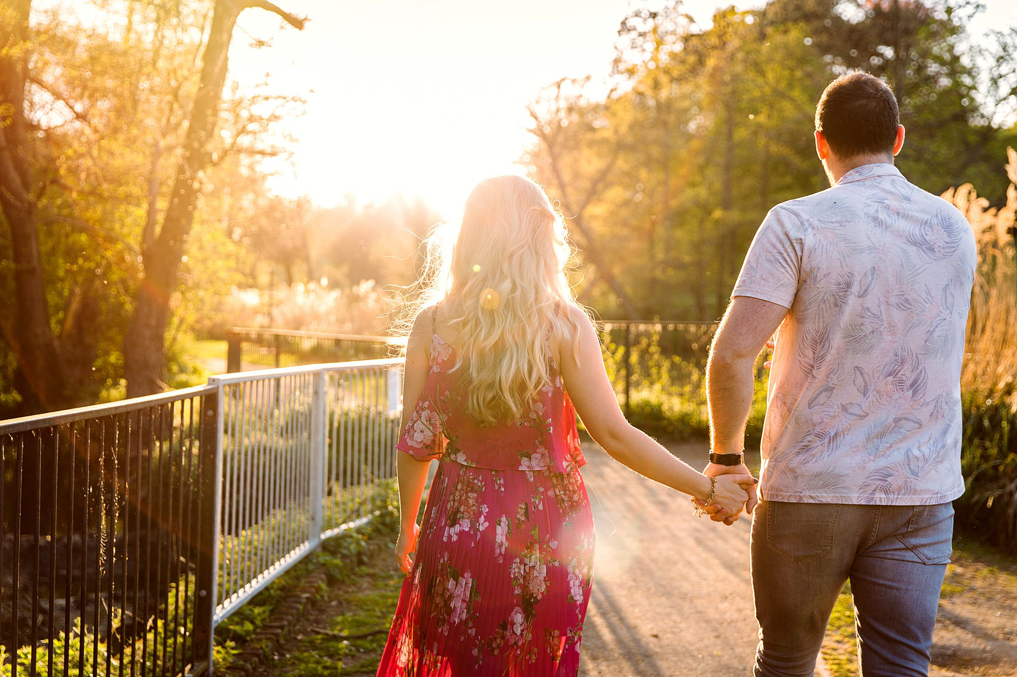 Summer evening engagement shoot couple walking in warm sunlight