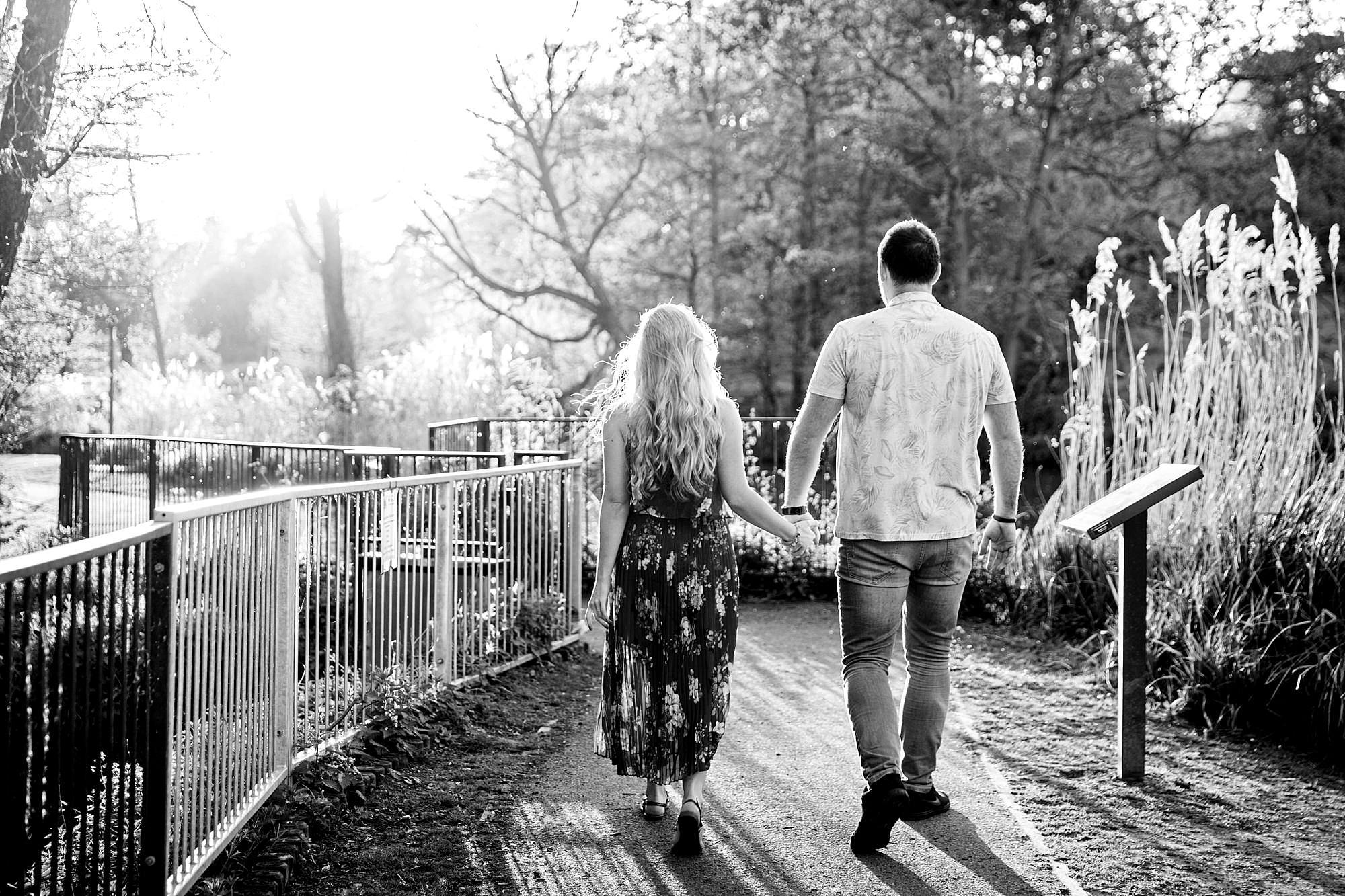 Summer evening engagement shoot couple walking through sunlit park