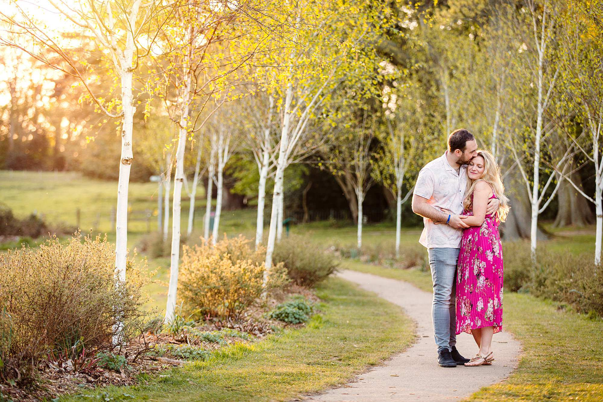 Summer evening engagement shoot couple cuddle together on pathway