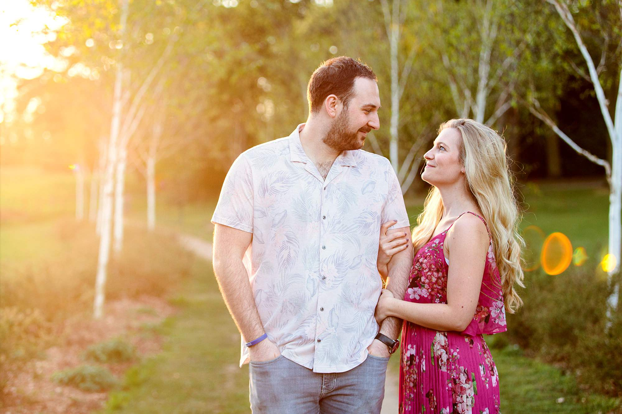 Summer evening engagement shoot couple chat together in sunlit park