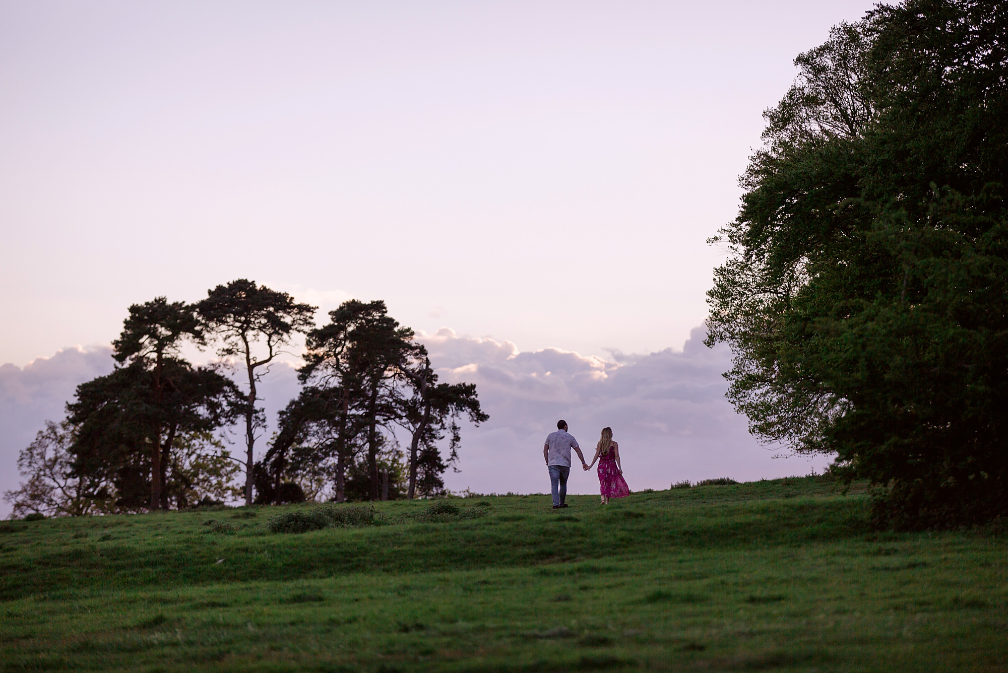 couple walk together forwards clouds on Summer evening engagement shoot