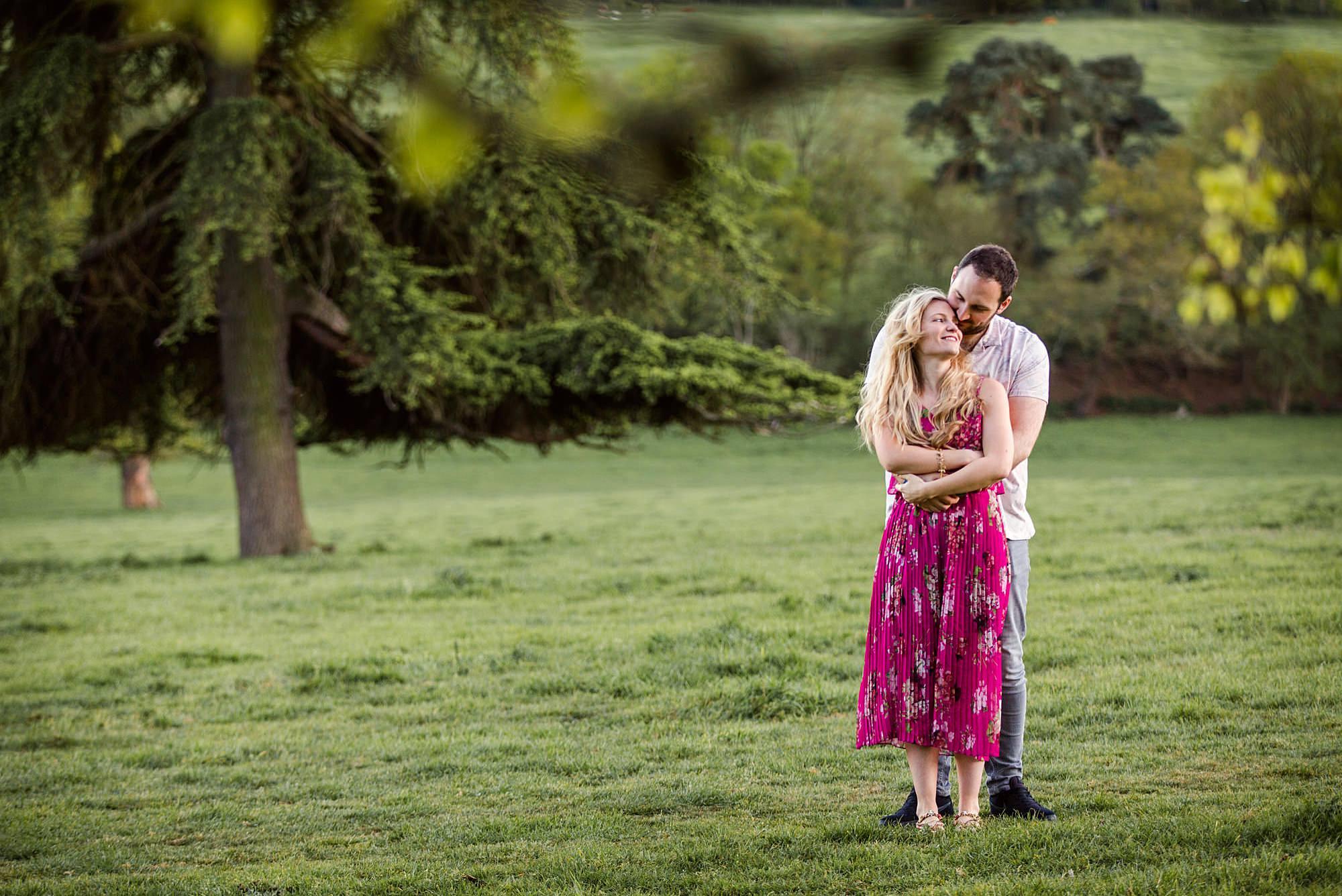 Summer evening engagement shoot couple hug in field