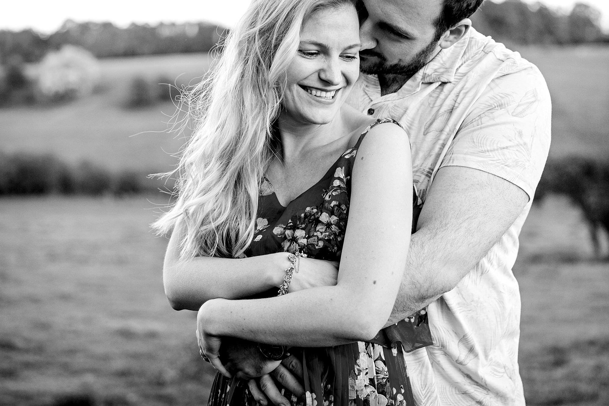 Summer evening engagement shoot couple cuddle tightly