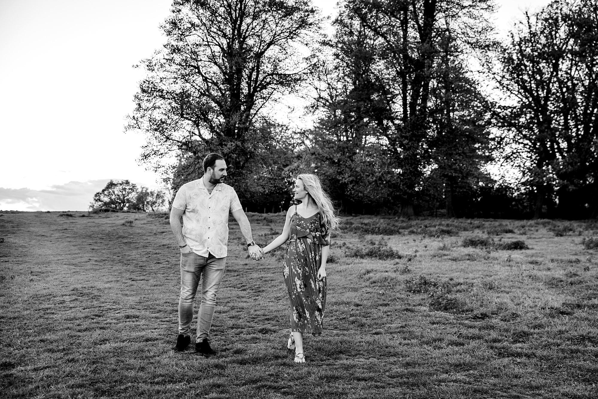 Summer evening engagement shoot couple walk together through park