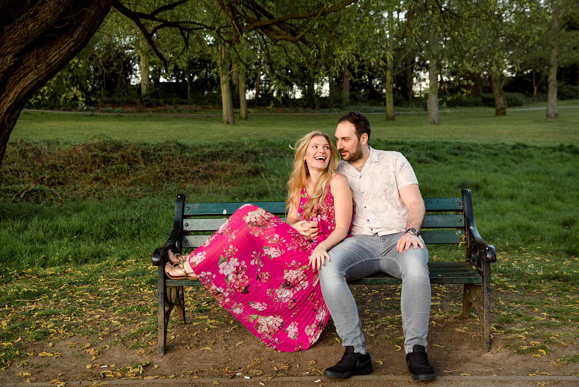 Summer evening engagement shoot couple laugh together on bench