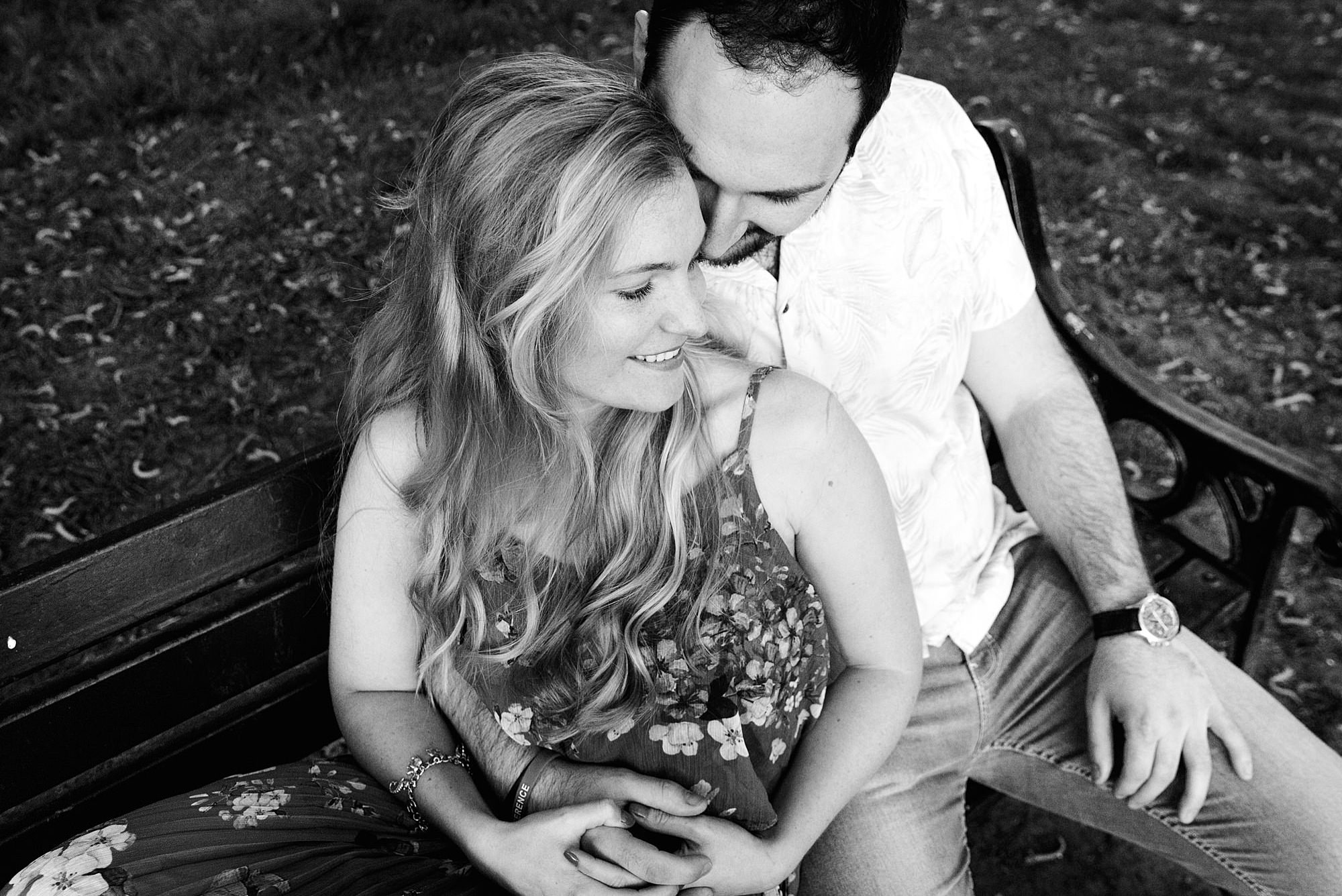 Summer evening engagement shoot couple cuddle together on park bench
