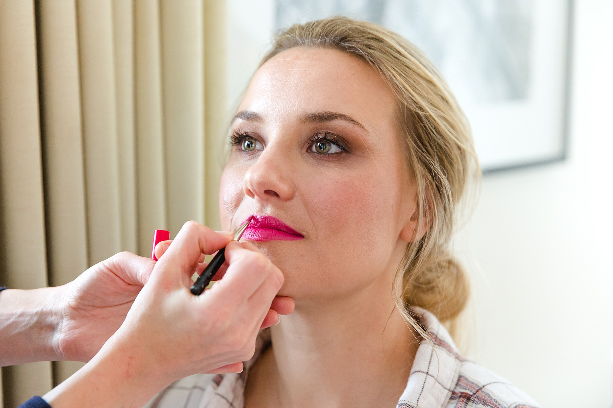 bride has bright pink lipstick applied