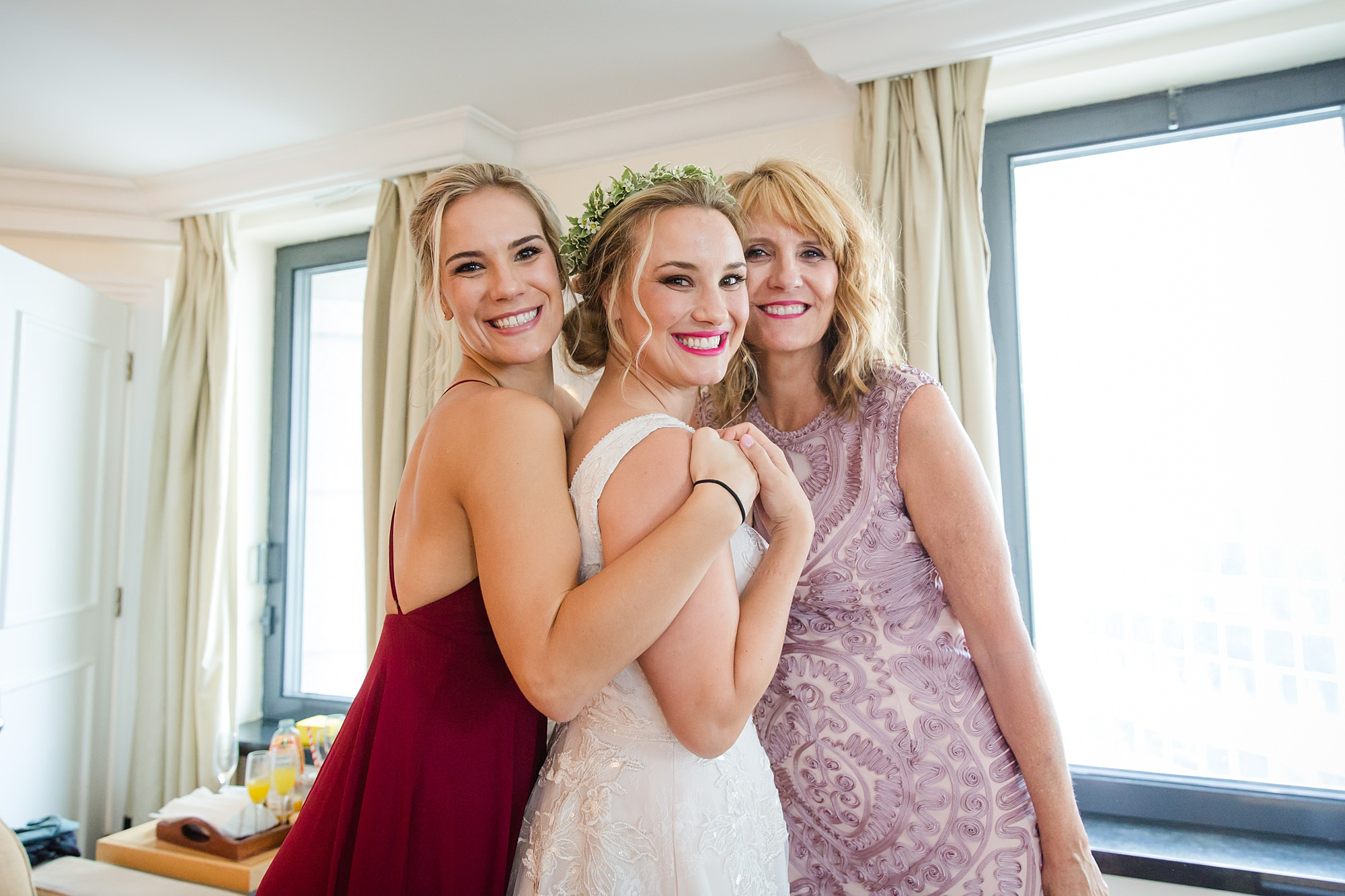 a bride smiles for a picture with her family