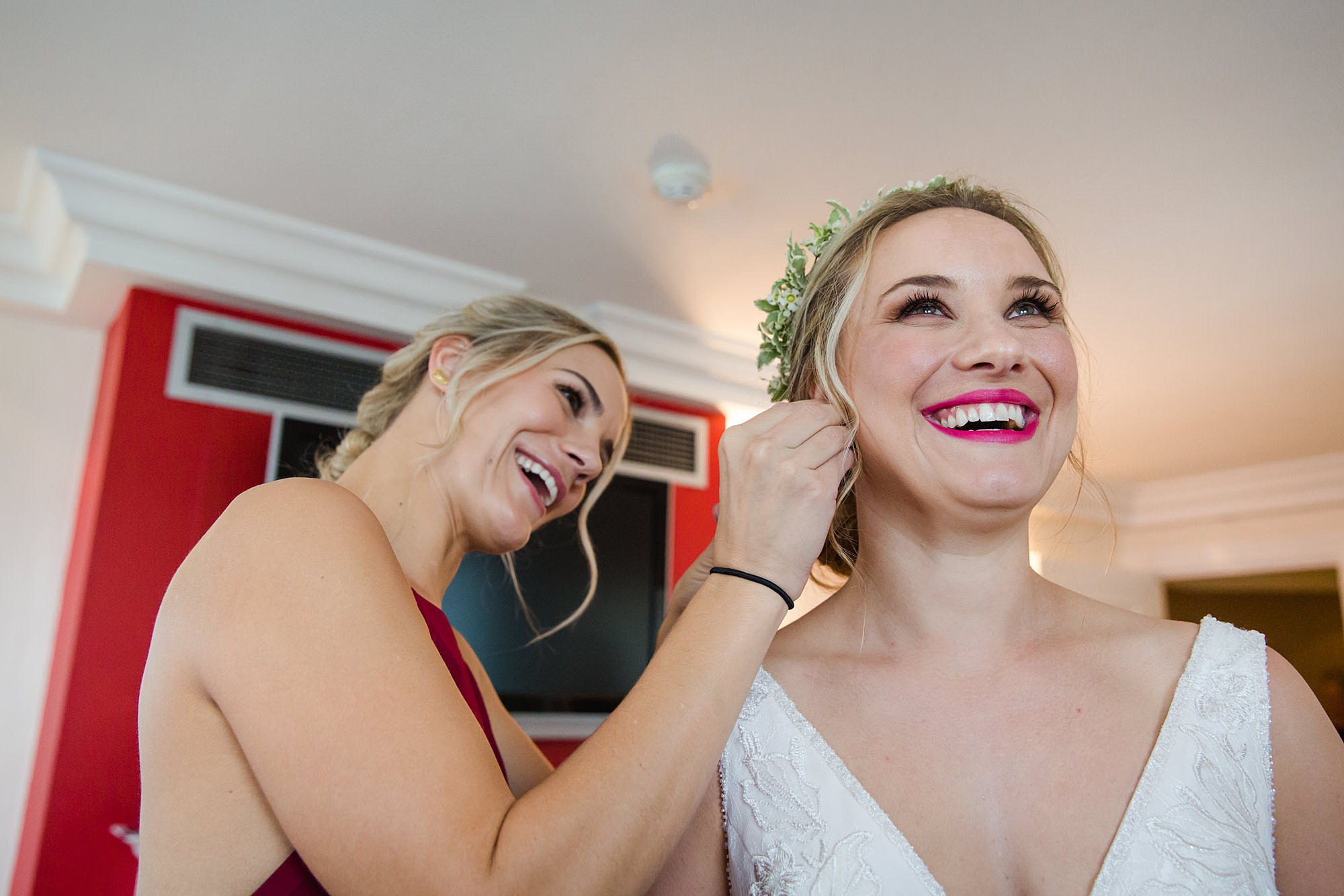 bridesmaid helping bride with earrings