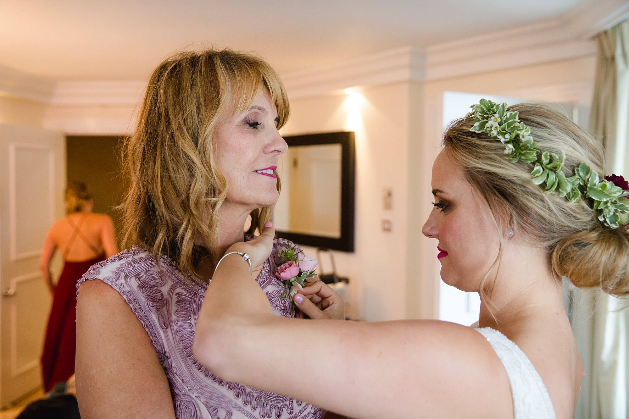 bride puts corsage on her mum