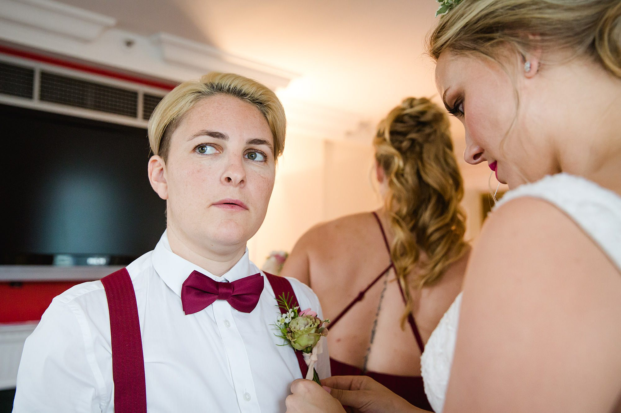 bride puts corsage on bridesmaid