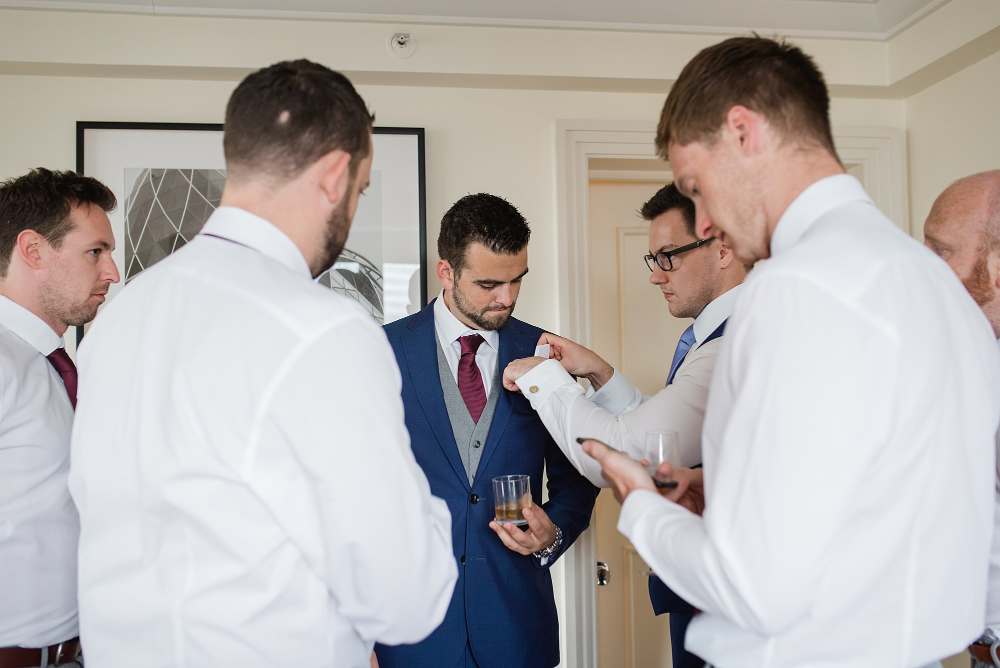 groomsmen help groom with pocket square