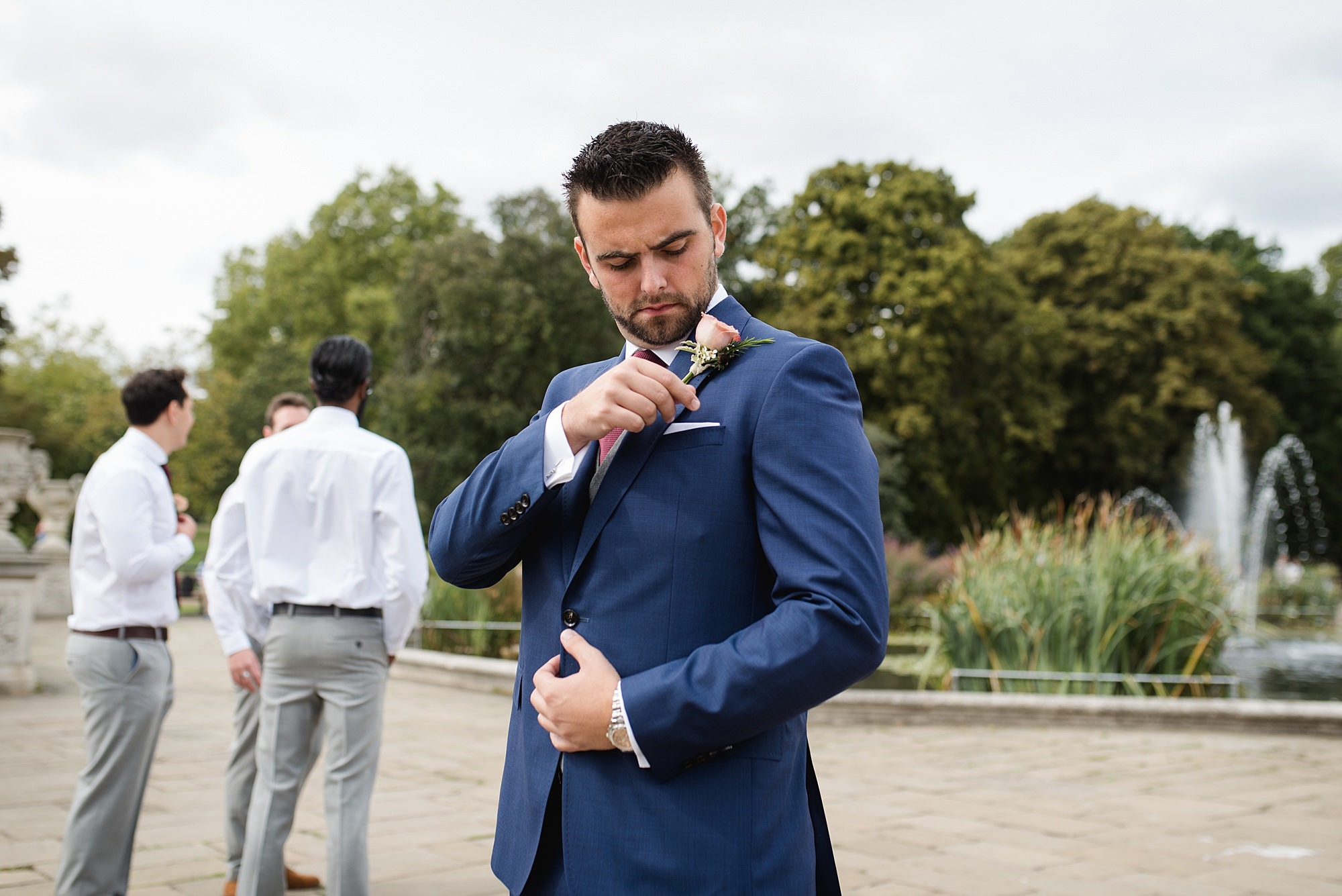 groom adjusts his buttonhole