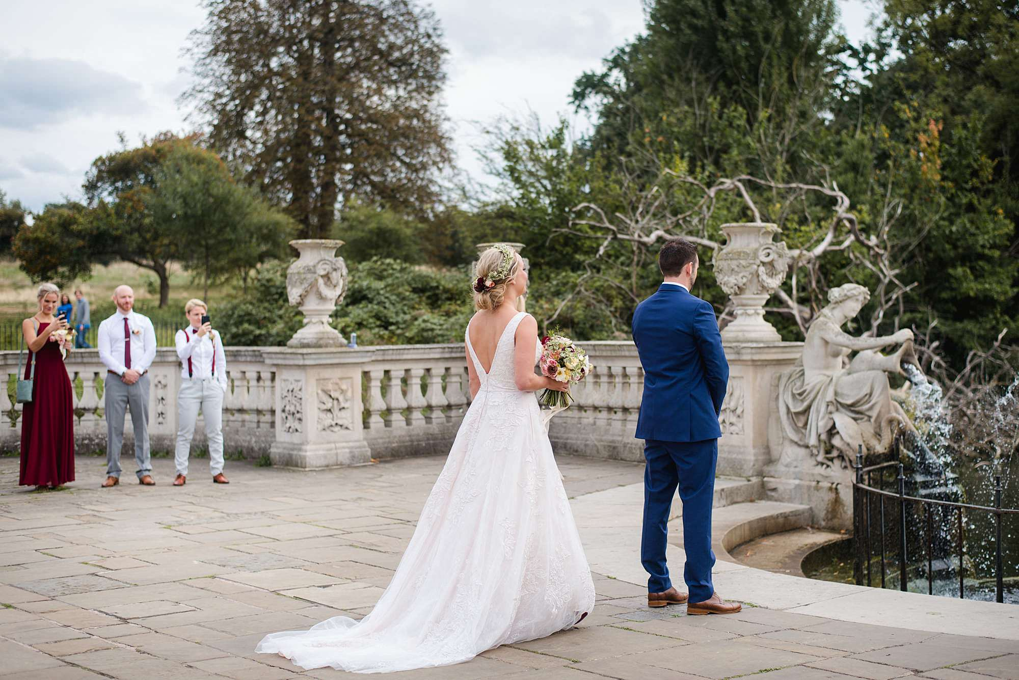 bride walks towards groom in kensington park italian gardens