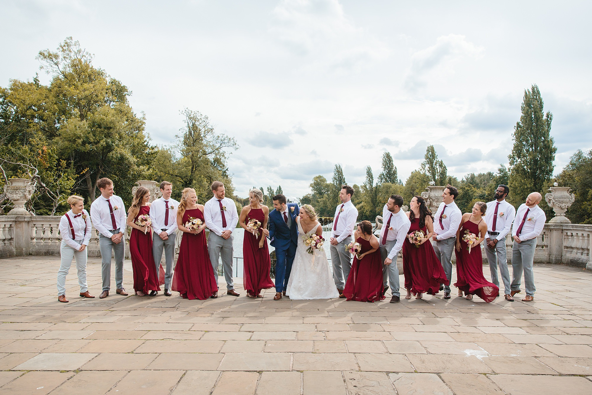 a wedding party laughs together at italian gardens