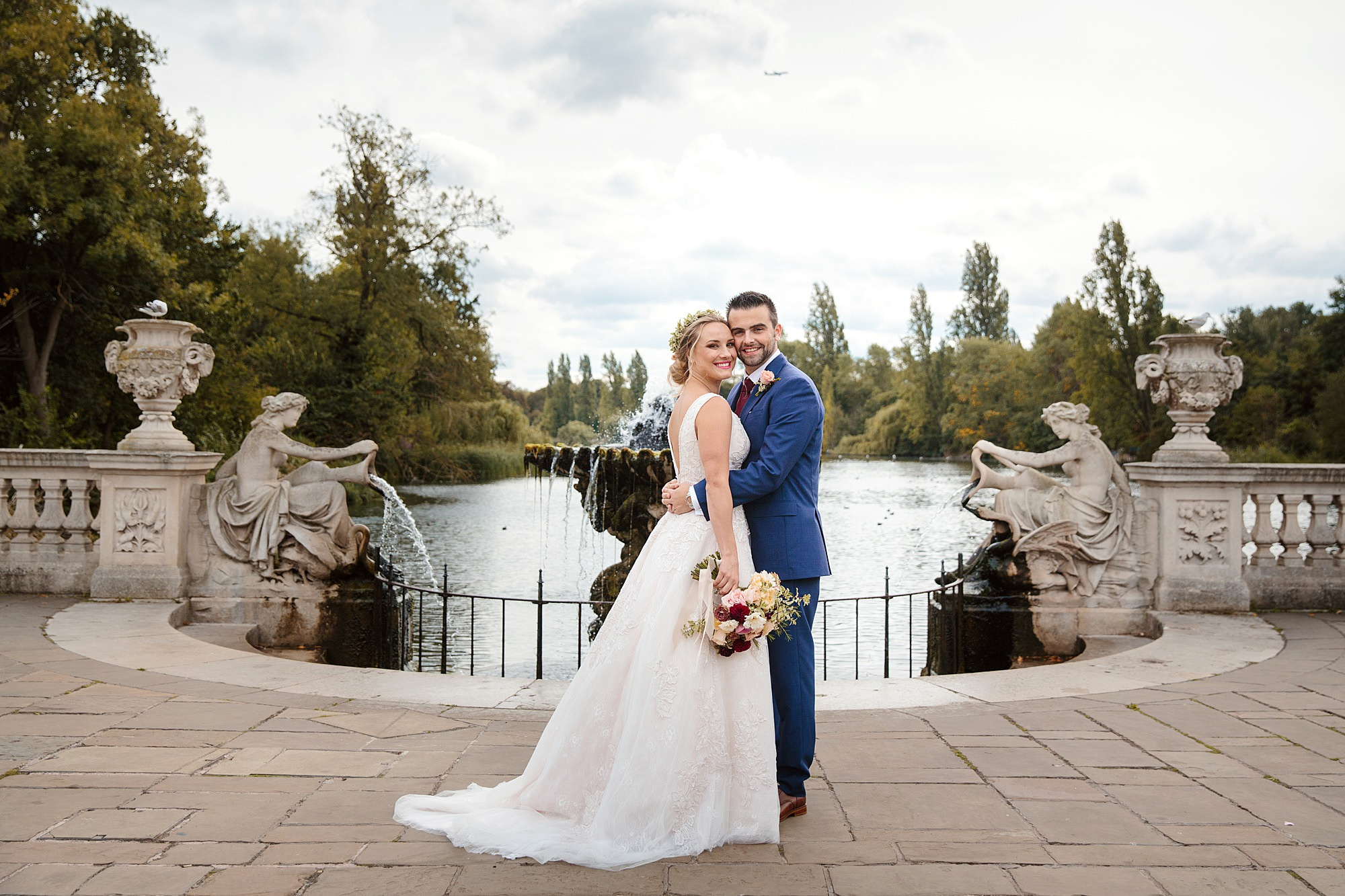 bride and groom in front of fountain at italian gardens
