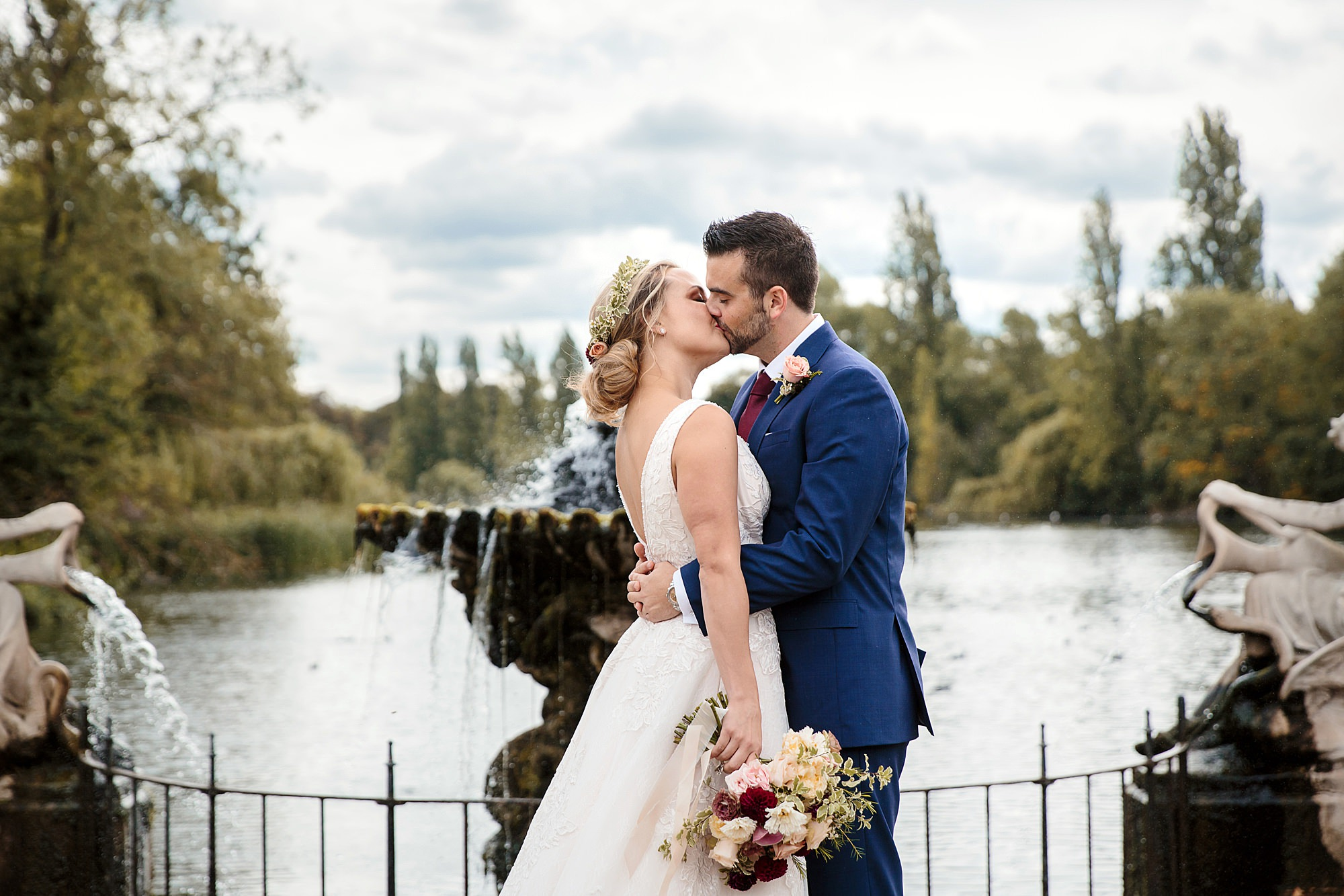 bride and groom kiss in front of kensington park fountain