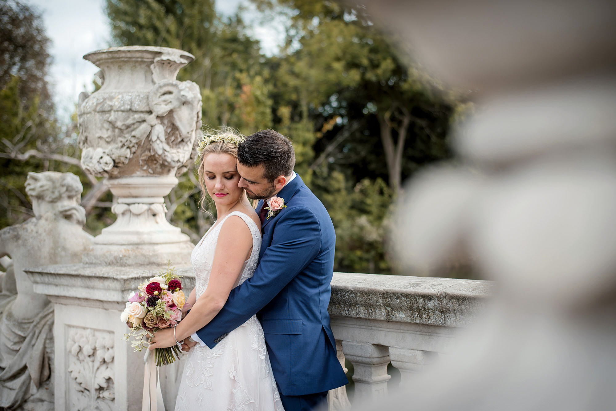 groom cuddles up to his bride in italian gardens kensington