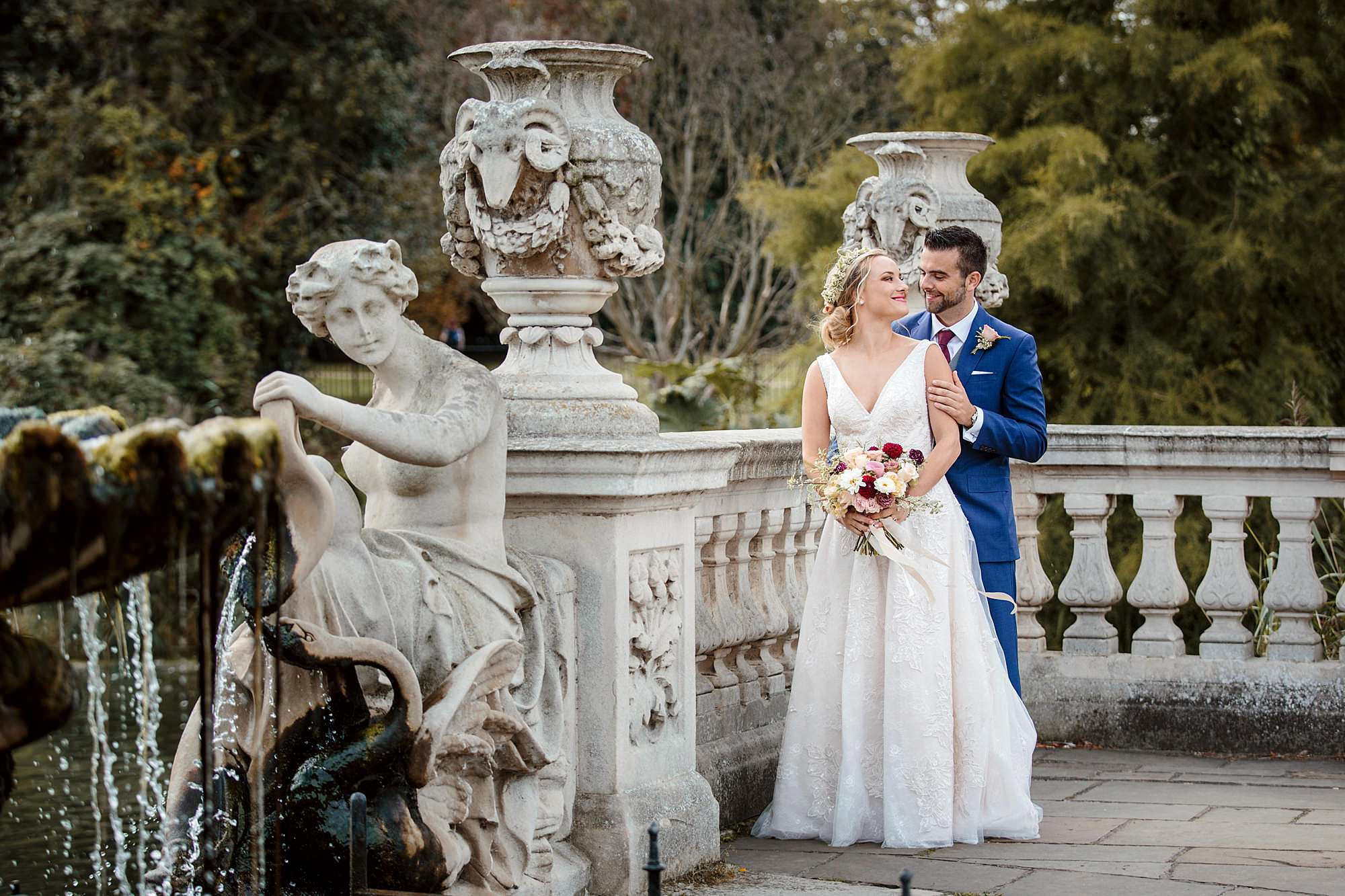 bride and groom by ornate wall in italian gardens