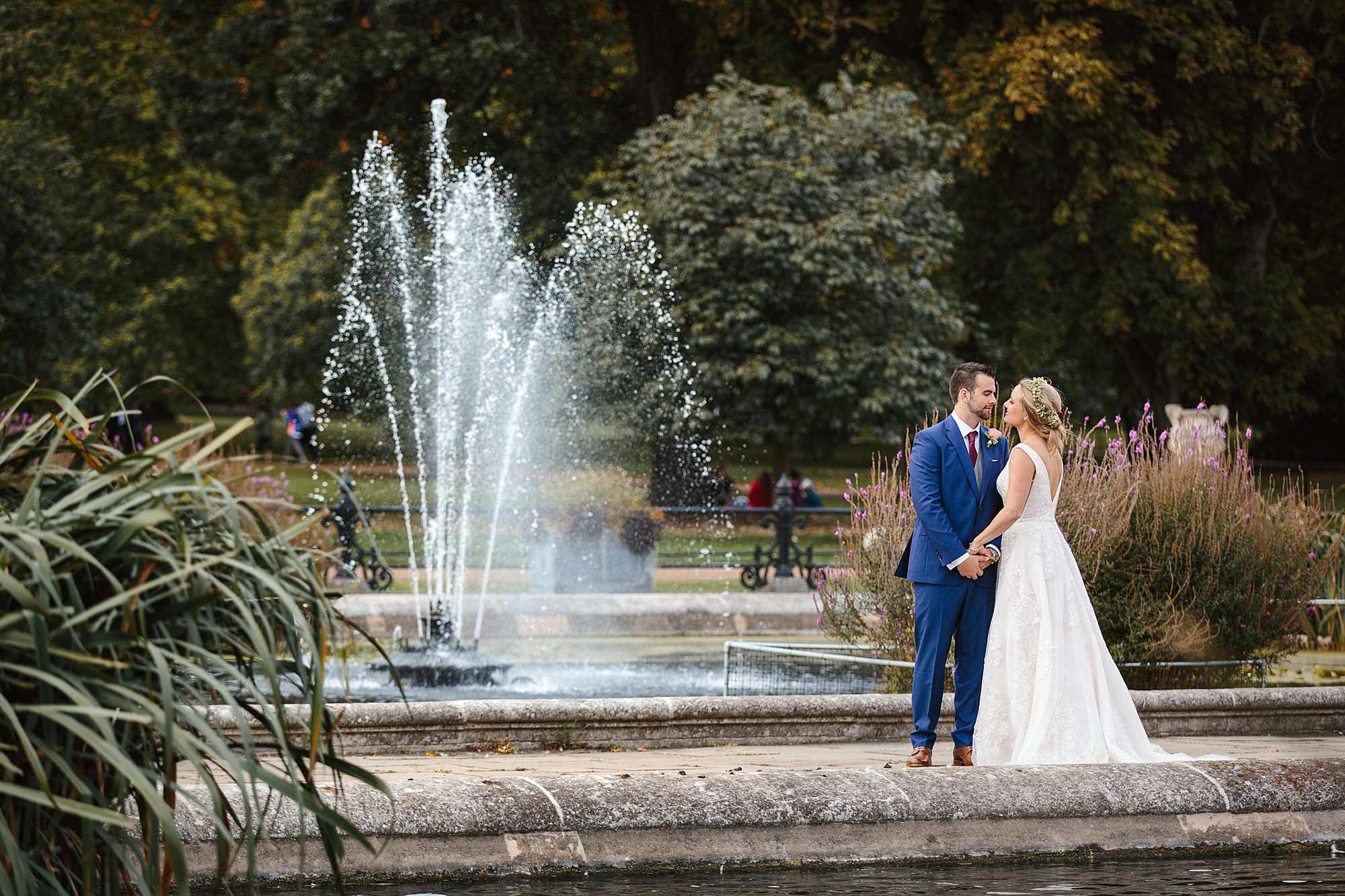 bride and groom by fountain and ponds in kensington gardens