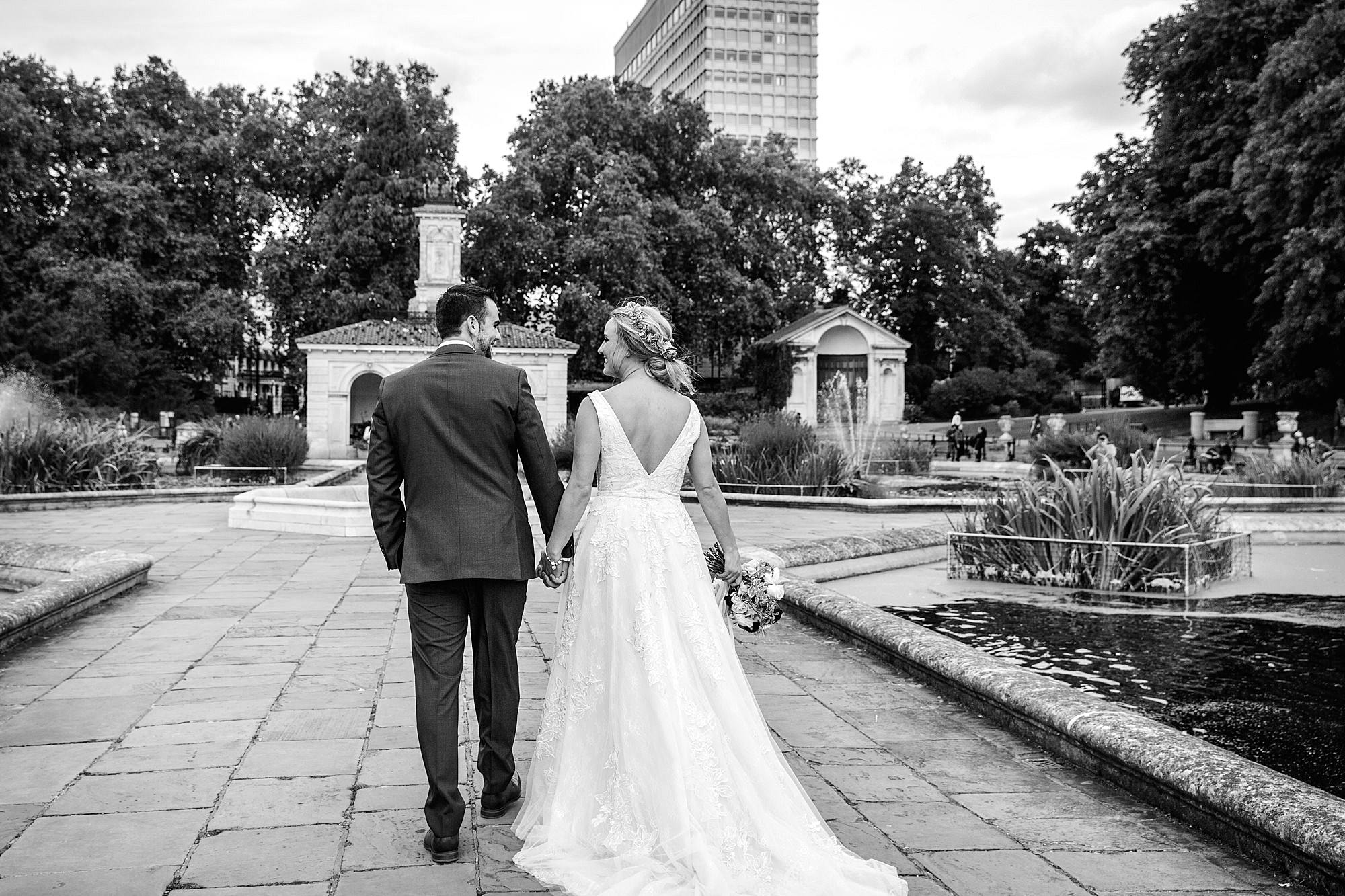 bride and groom walking through italian gardens in kensington