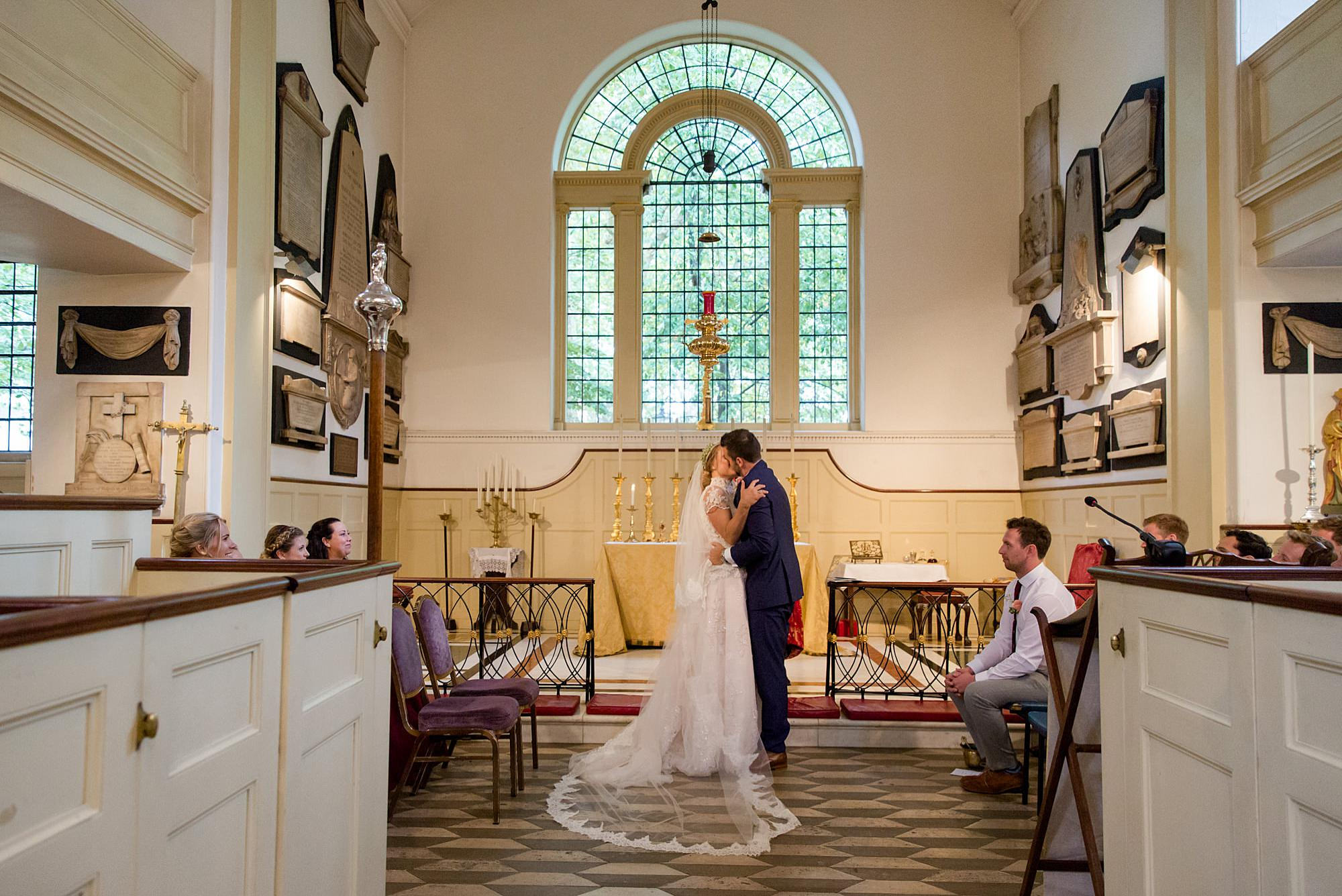 bride and groom first kiss in paddington church wedding