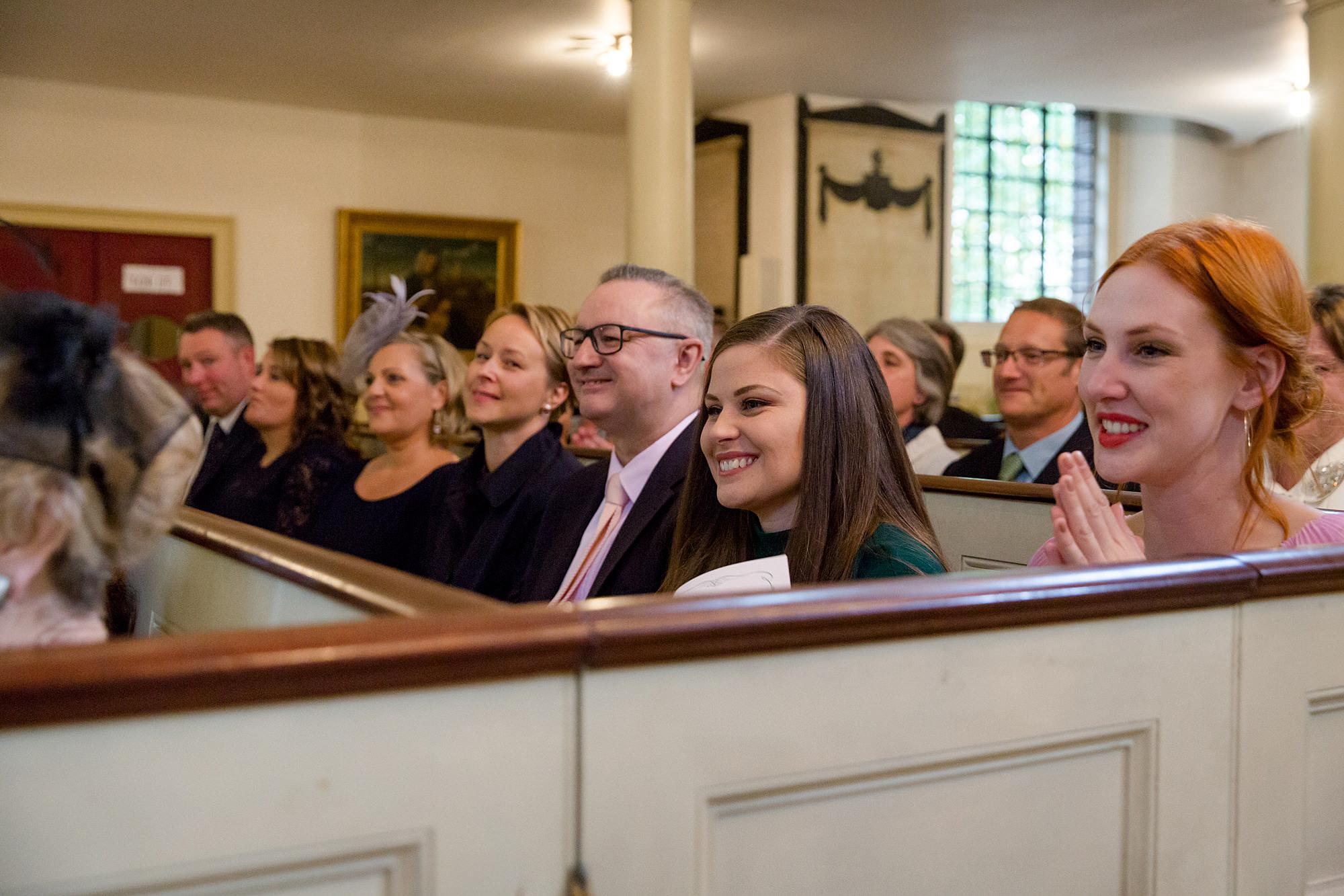 wedding guests smile during ceremony