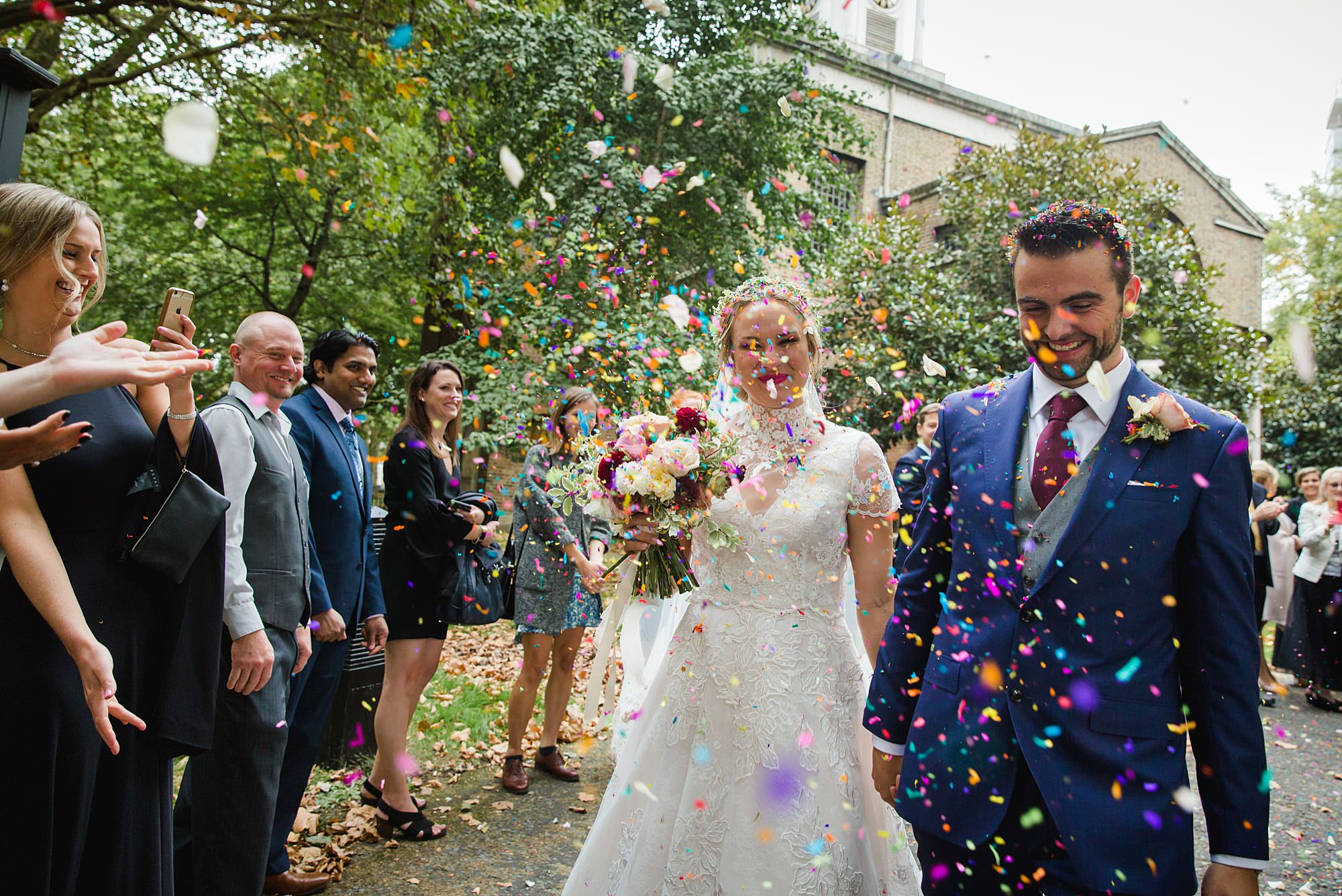 bride and groom in colourful confetti after ceremony