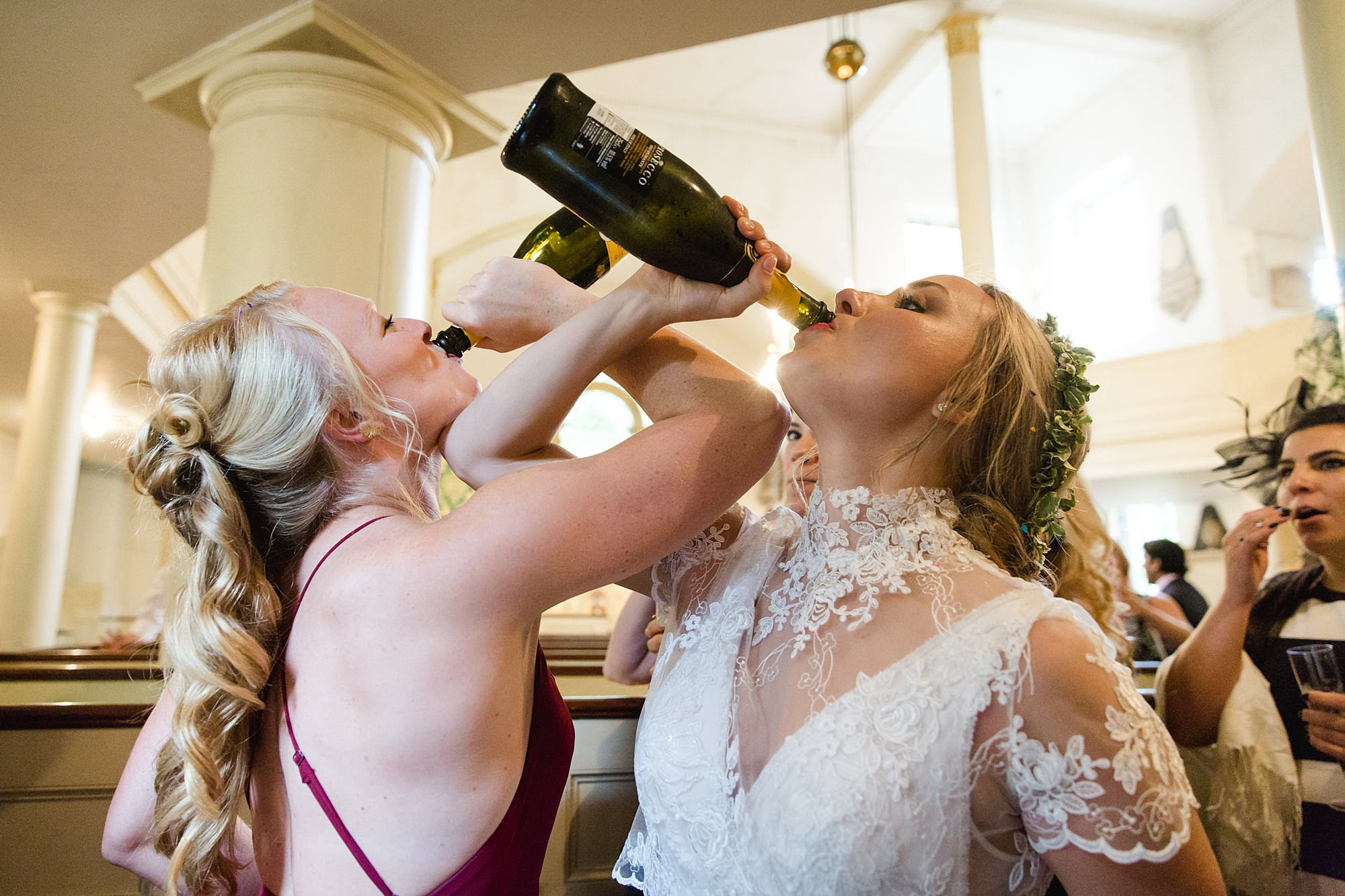 bride and bridesmaid swig from champagne bottle