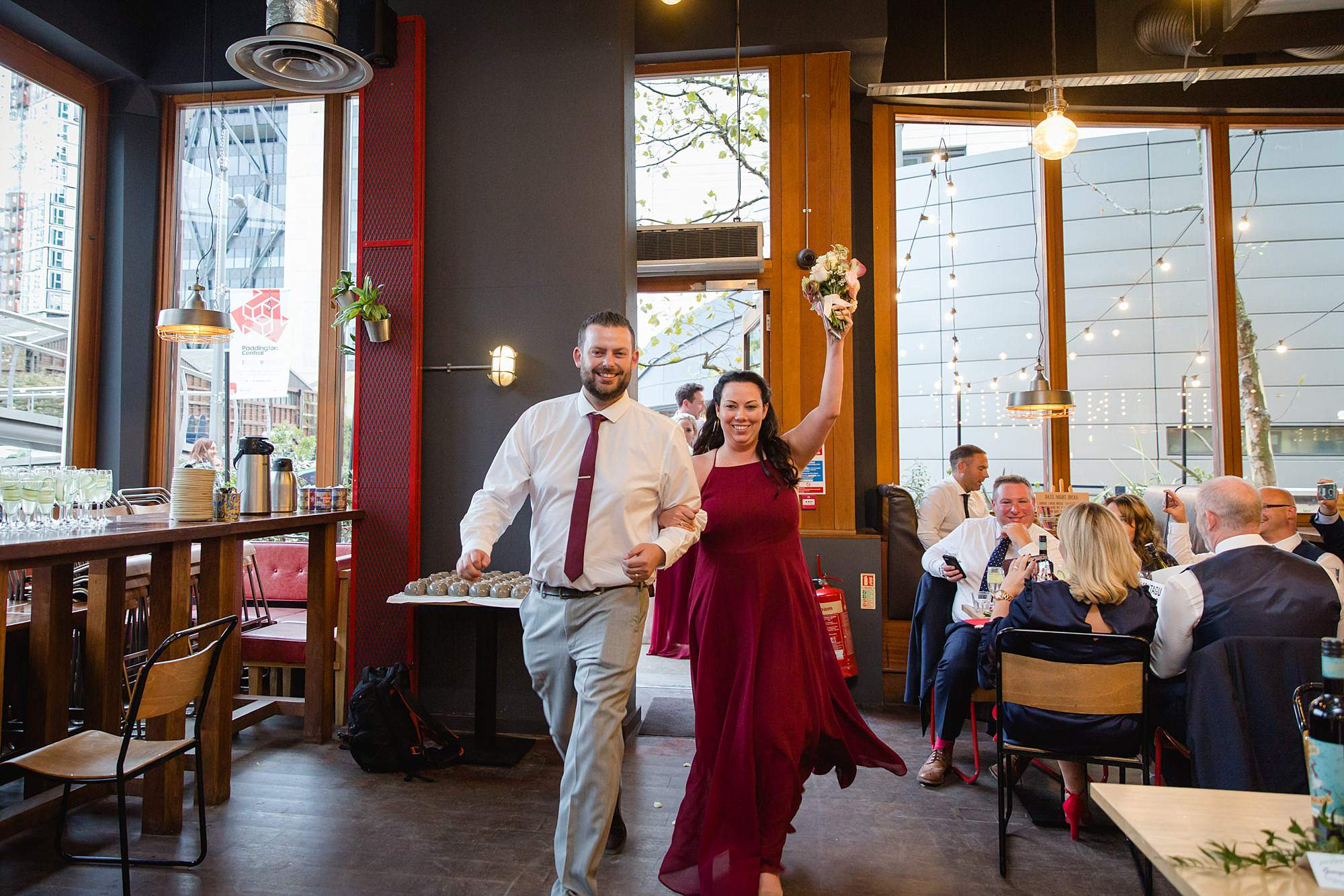 bridesmaid and groomsman cheer as they enter The Union Paddington wedding reception
