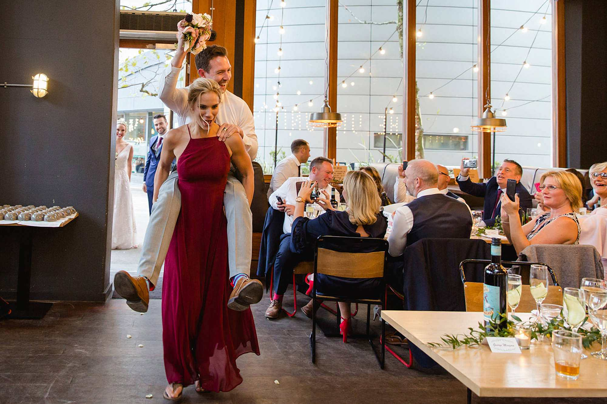 bridesmaid carries groomsman into wedding reception